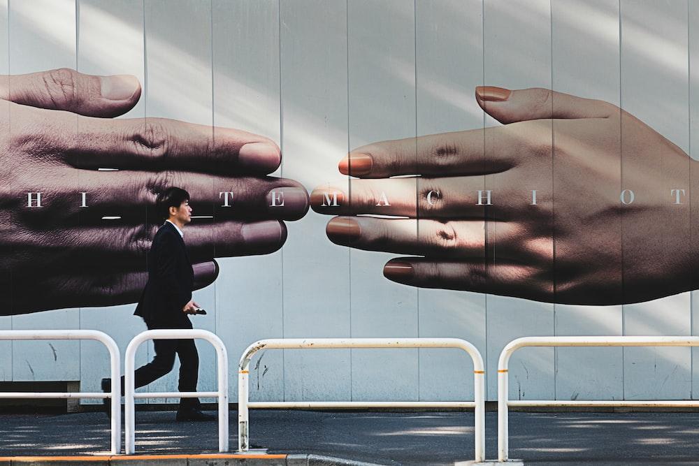 man walking on sidewalk beside hands mural