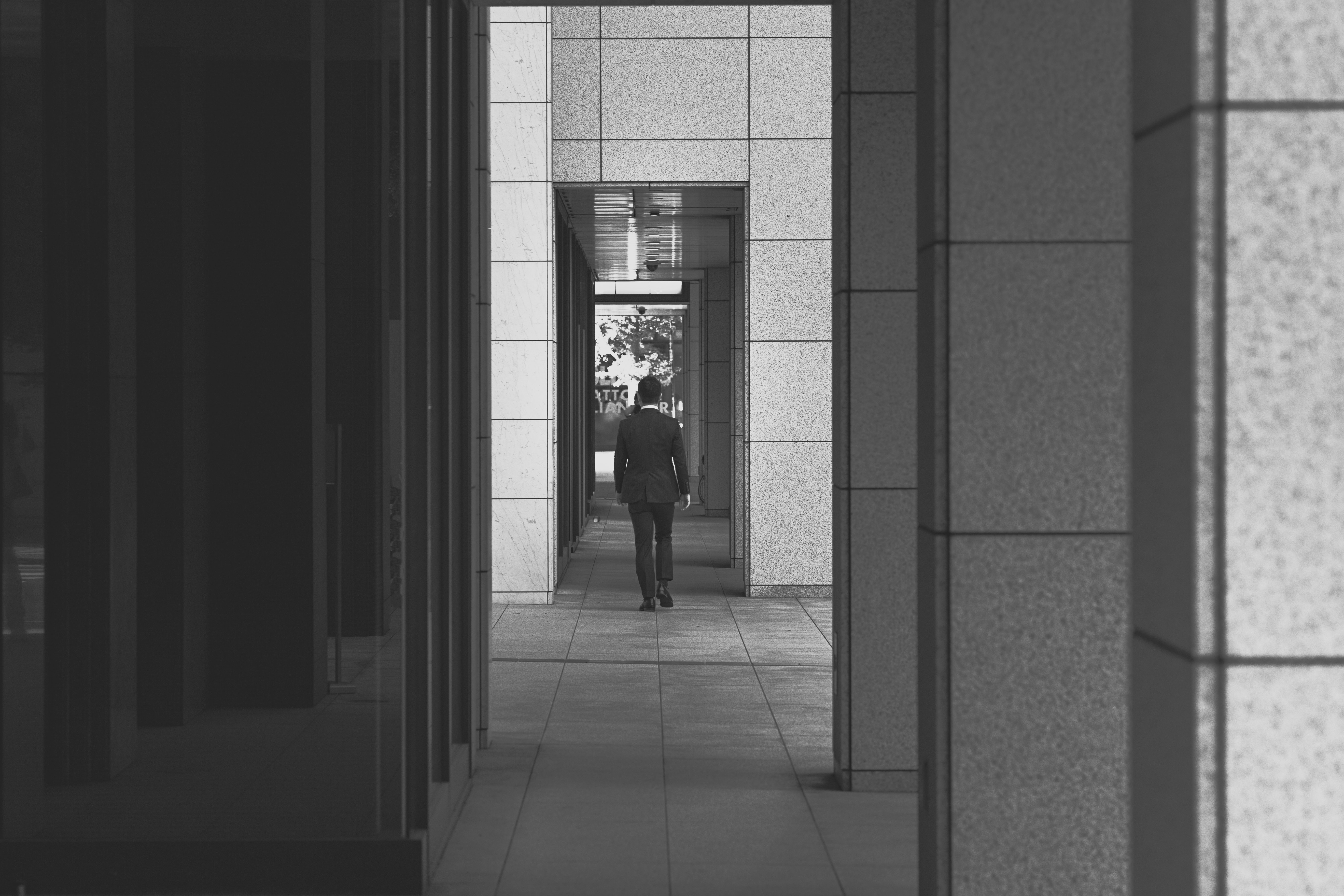 Black and white shot of person walking through outdoor corporate building hallway in suit