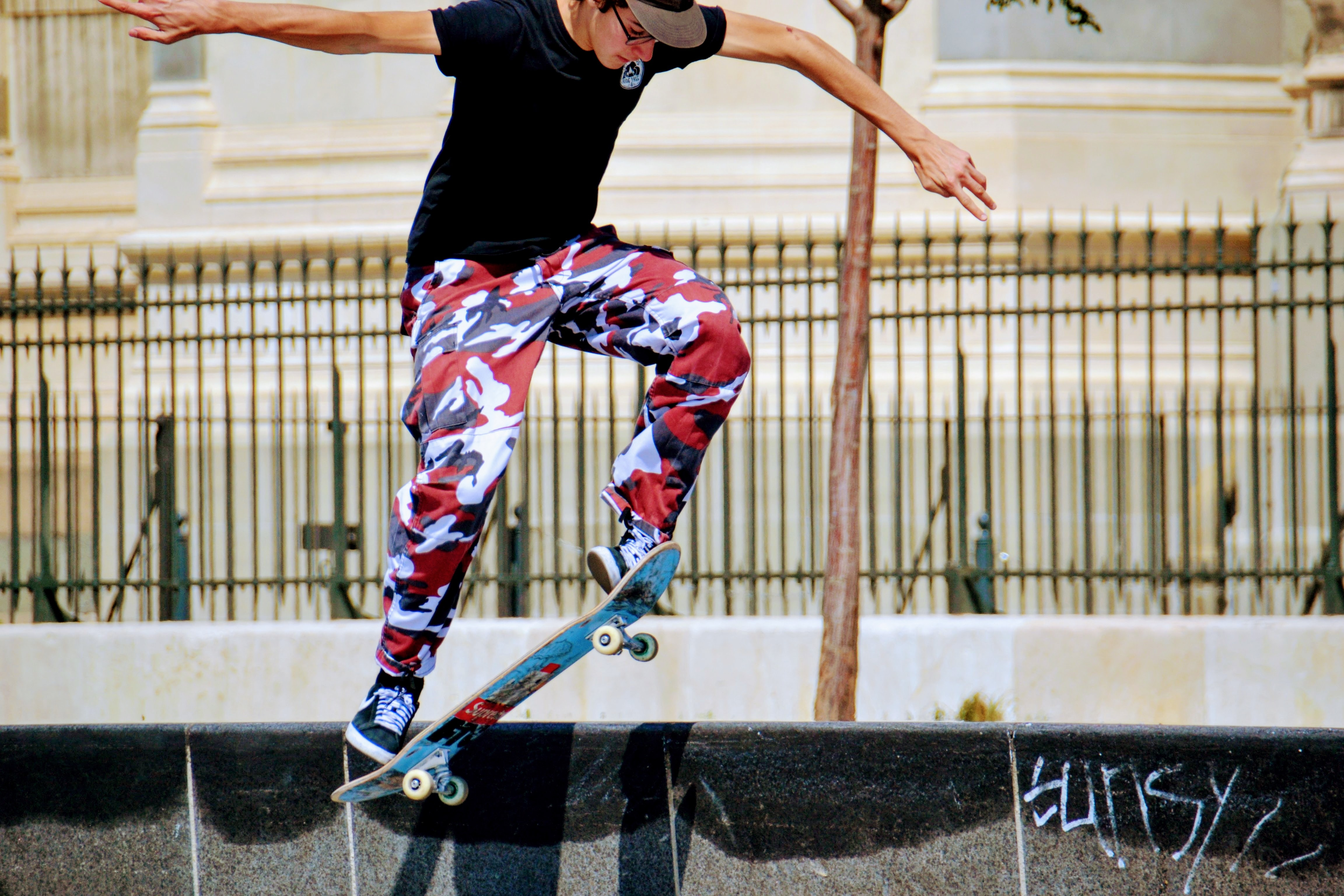 A person in a baseball cap and camouflage pants does a skateboard trick