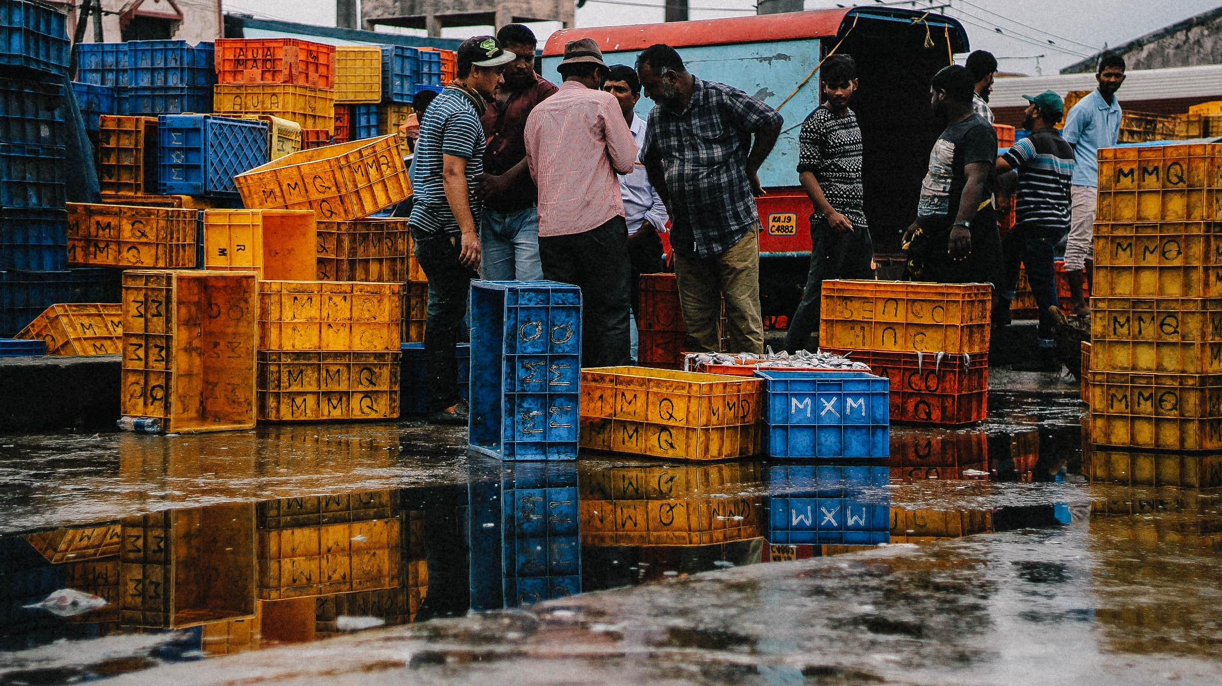 Men bargaining near crates with fish at a fish market
