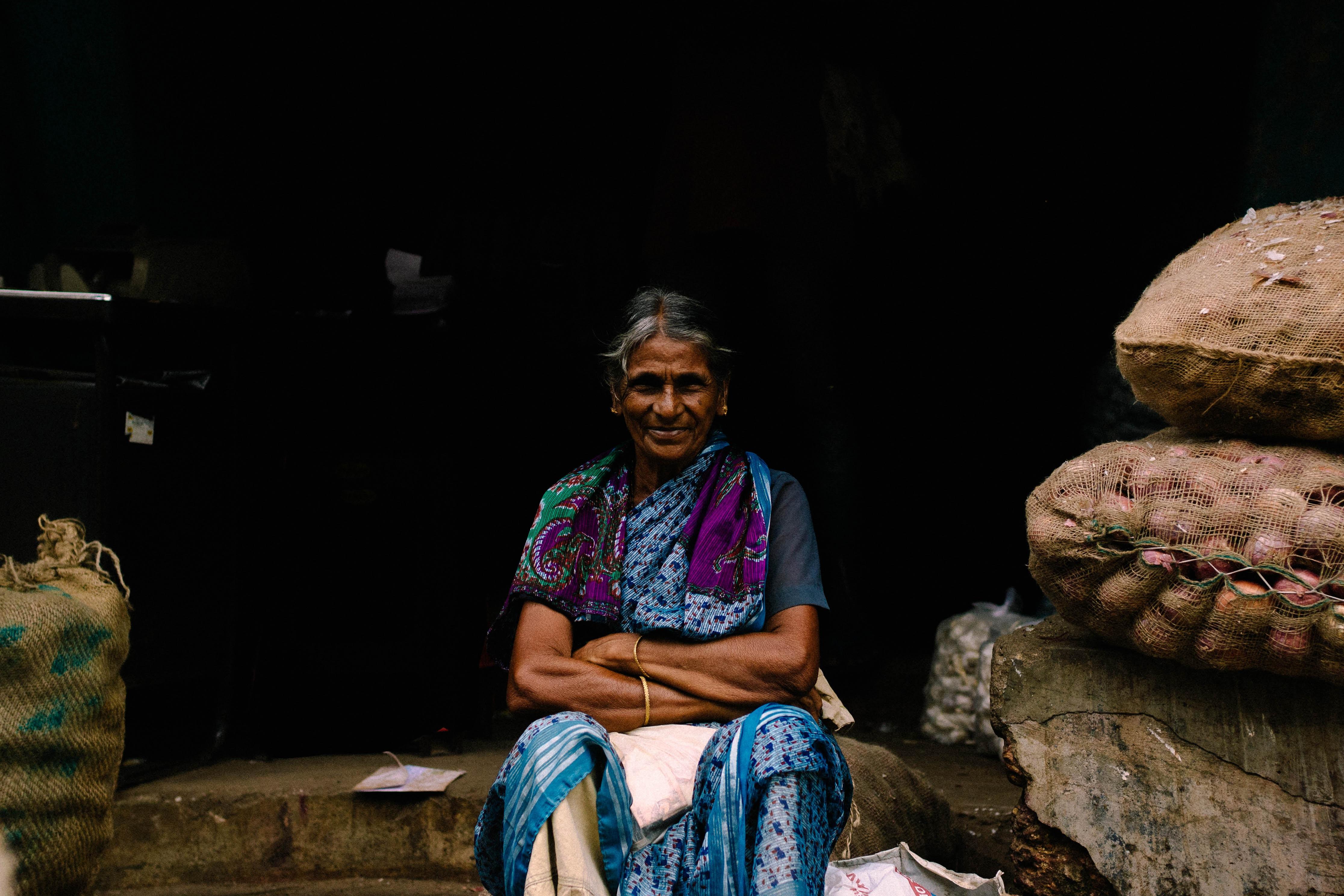 woman sitting near brown sacks