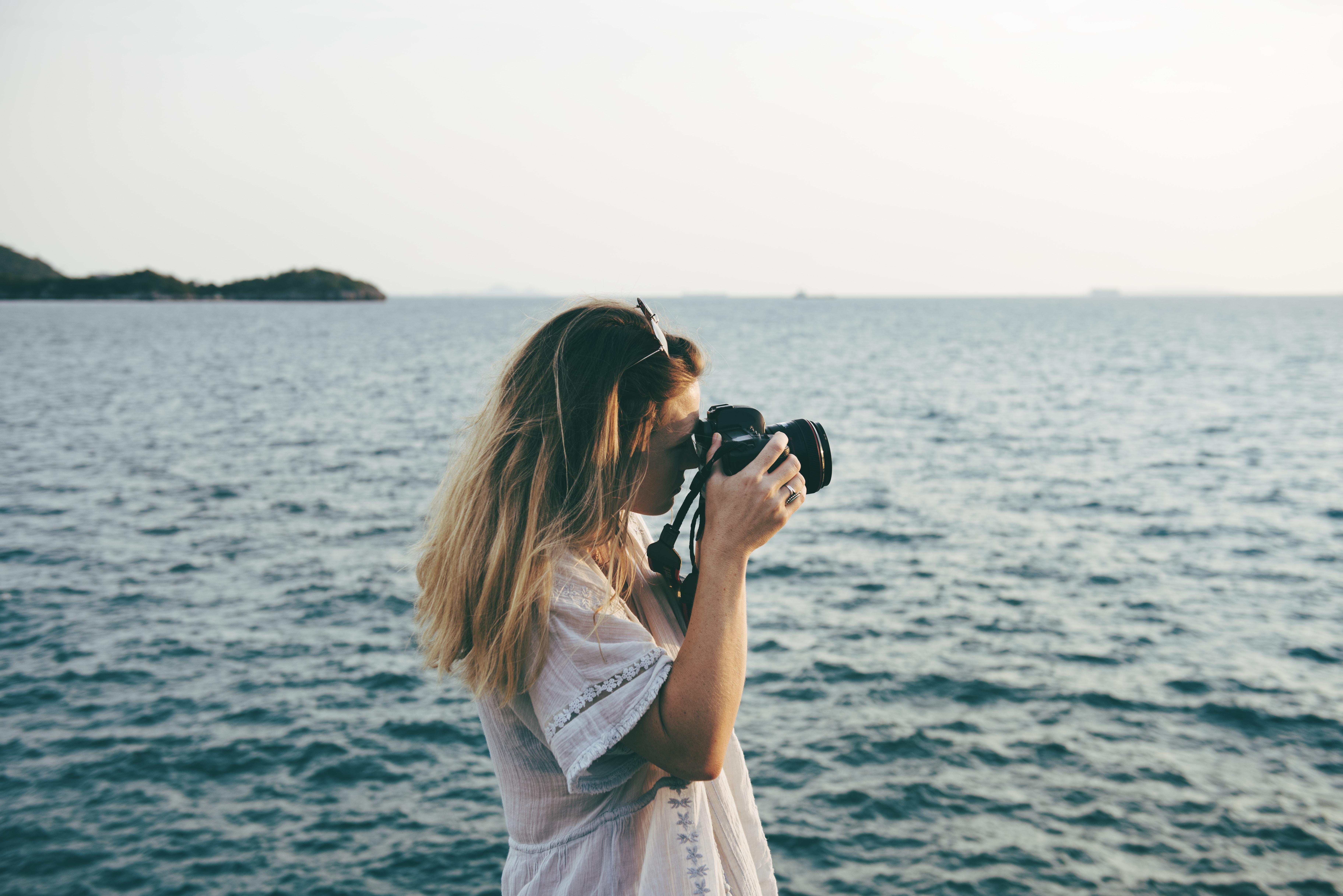 woman taking photo using her DSLR camera