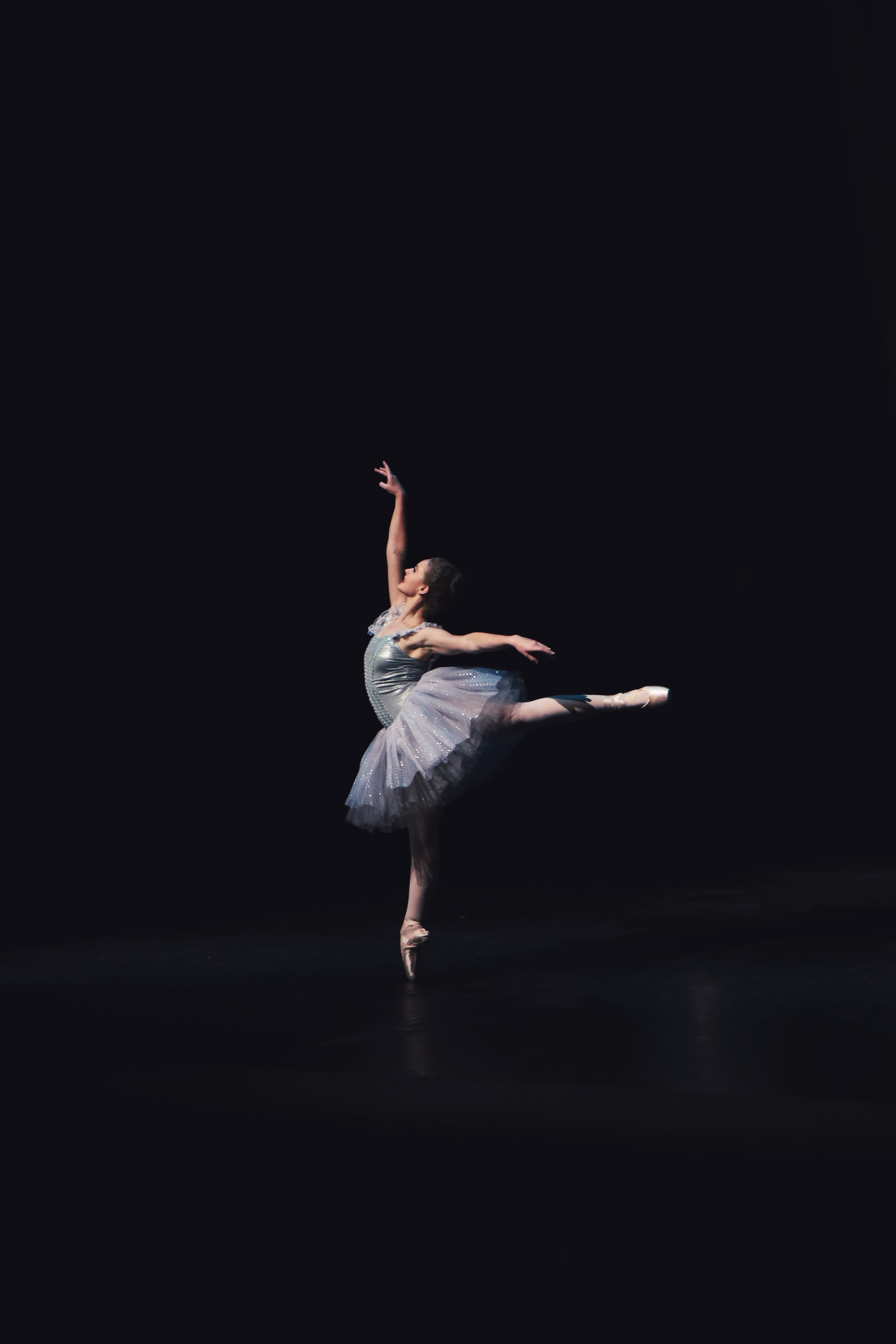Ballet dancer performing in rehearsal executing graceful pose in dark room