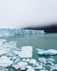 iceberg on body of water under cloudy sky