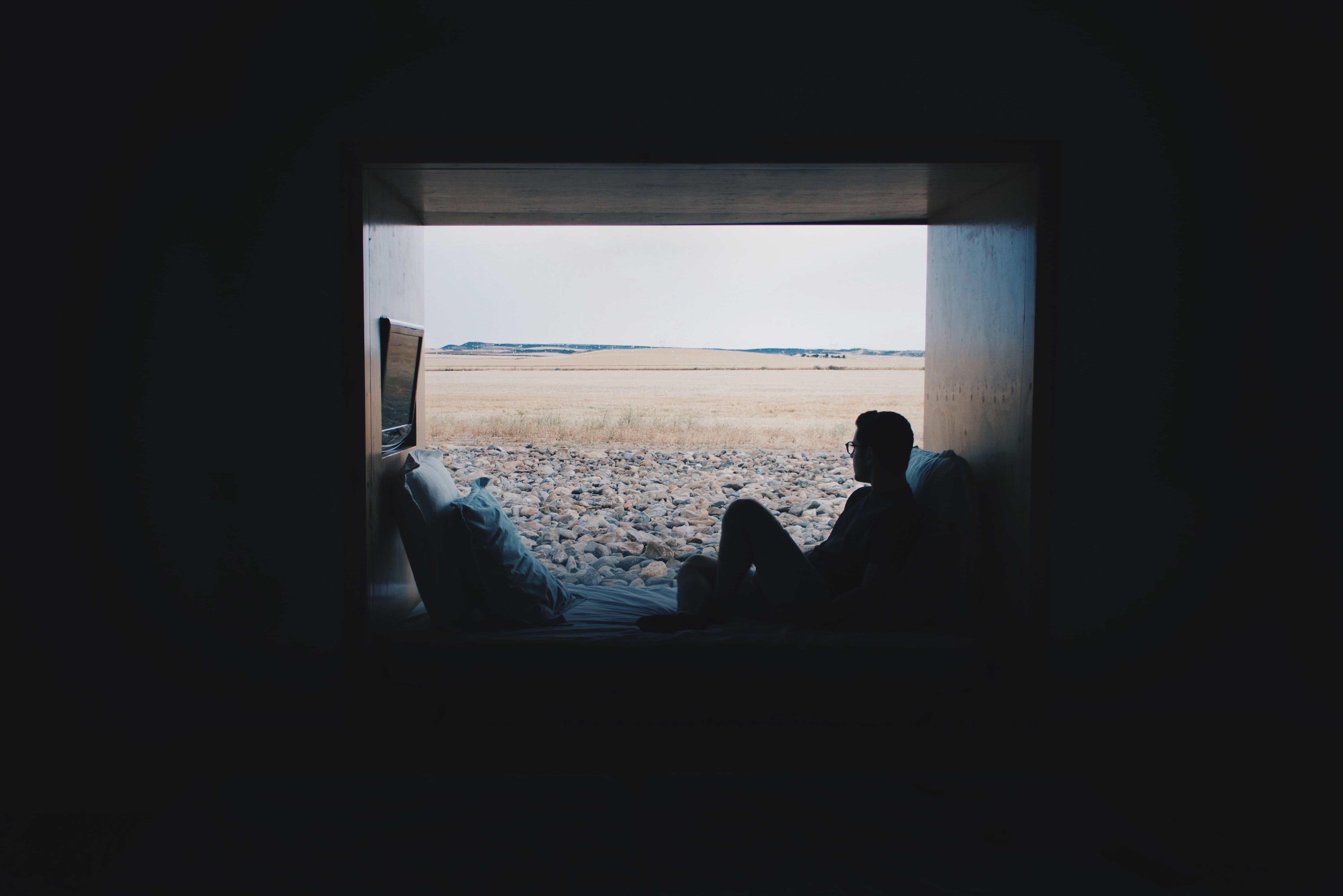 Man with glasses relaxing near window on sofa with rocky ground outside, Aire de Bardenas