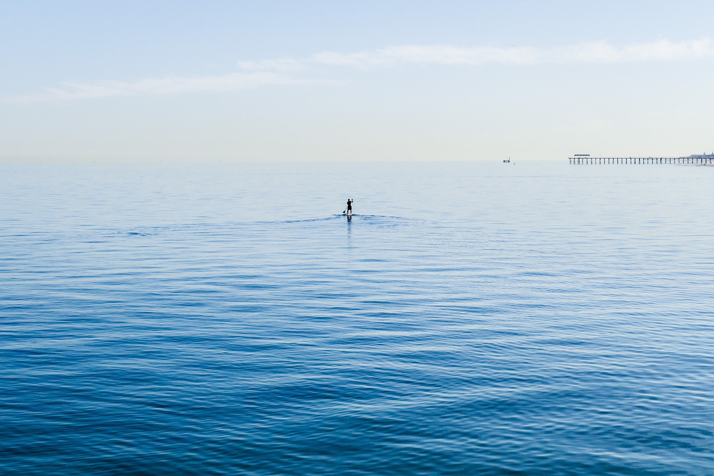 Person on a paddle board in the ocean with the pier in the distance at Henley Beach