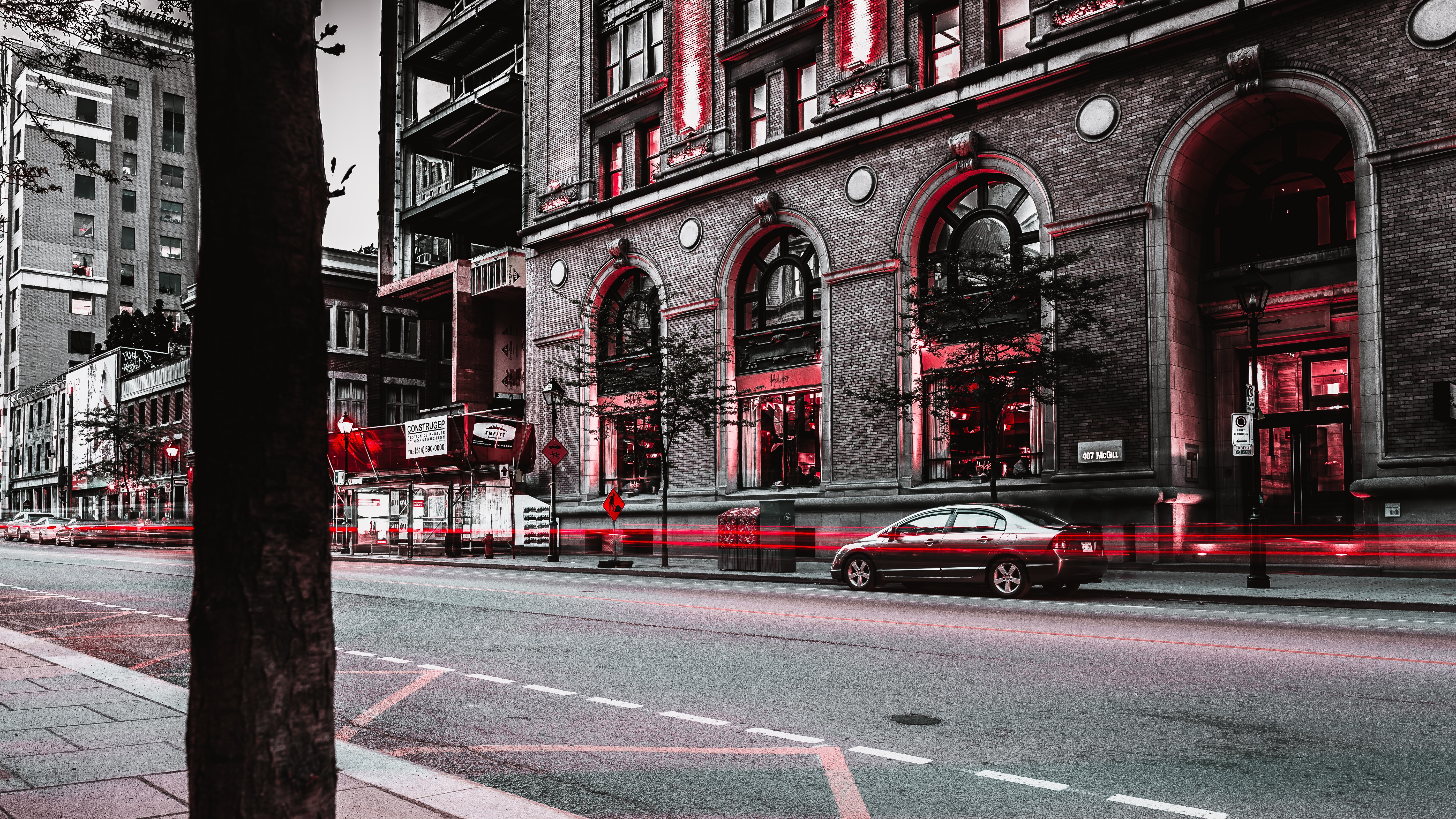 A classy shot of a city road in grey and red, with subtle red light trails