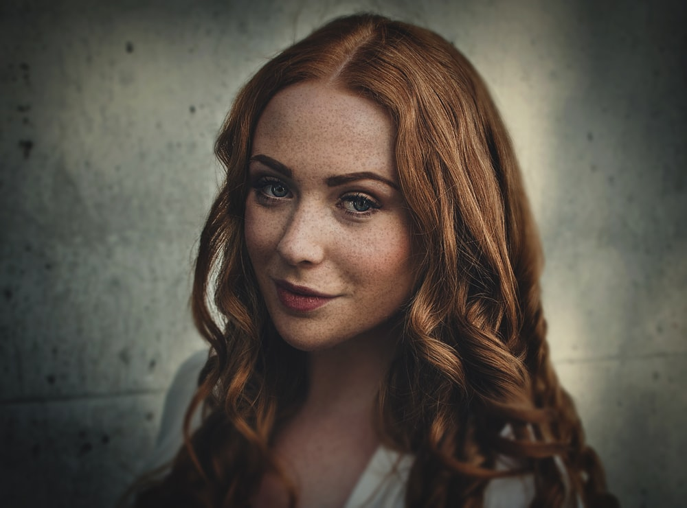 A woman with red hair, freckles, and crimson lipstick in front of a gray wall