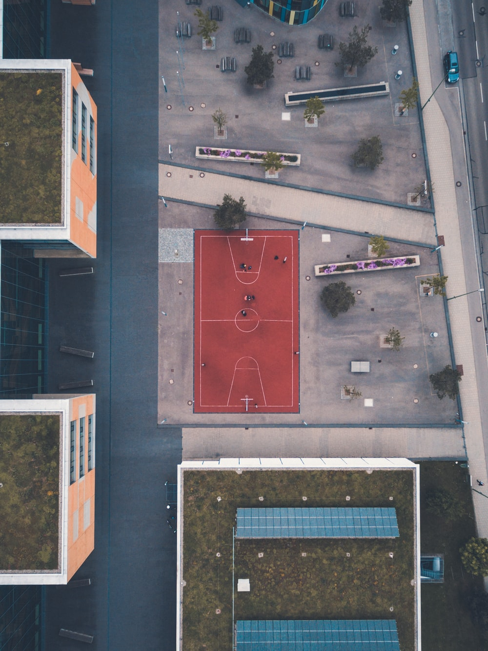 red basketball court near buildings in aerial photography