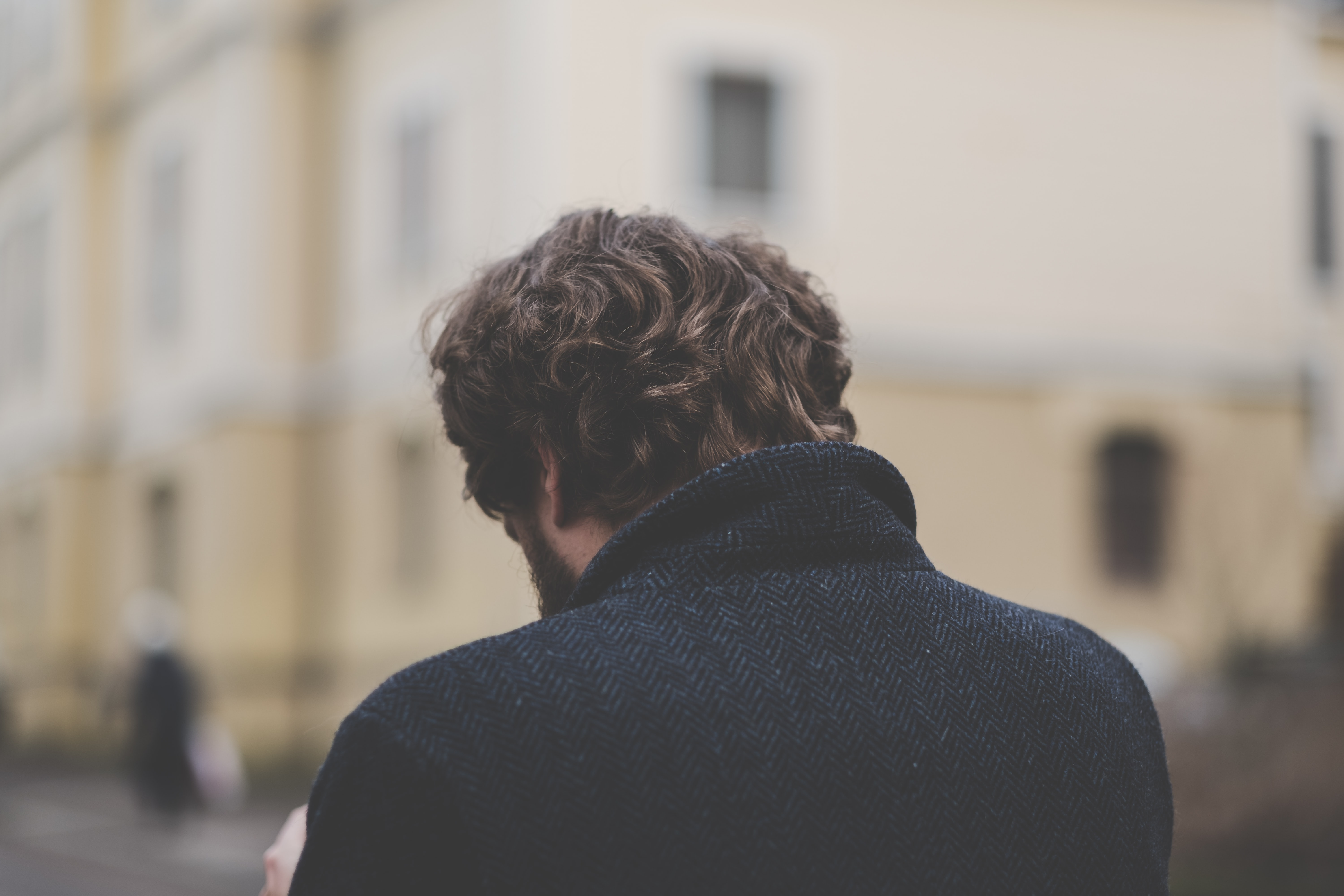The back of a man with his head bowed, thinking, outdoors in a city