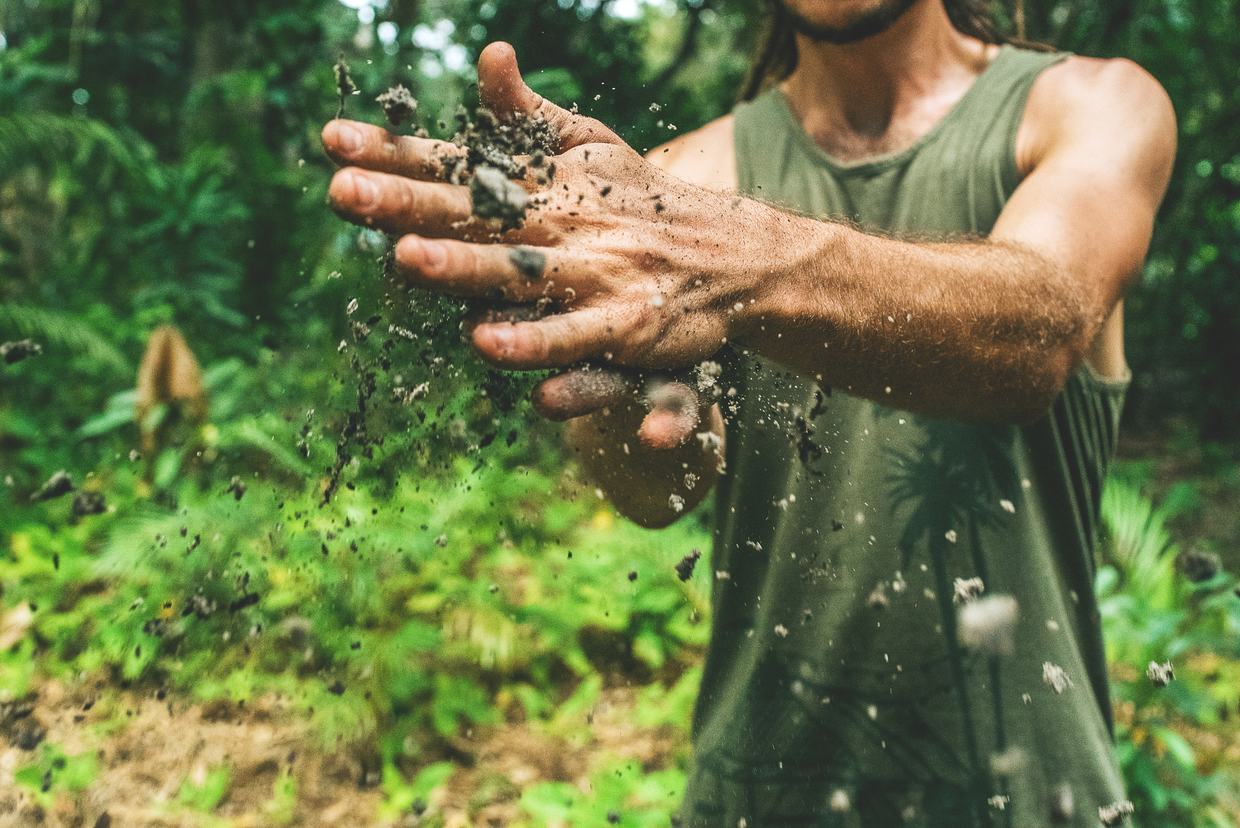 A man wiping dirt off of his hands in the jungle