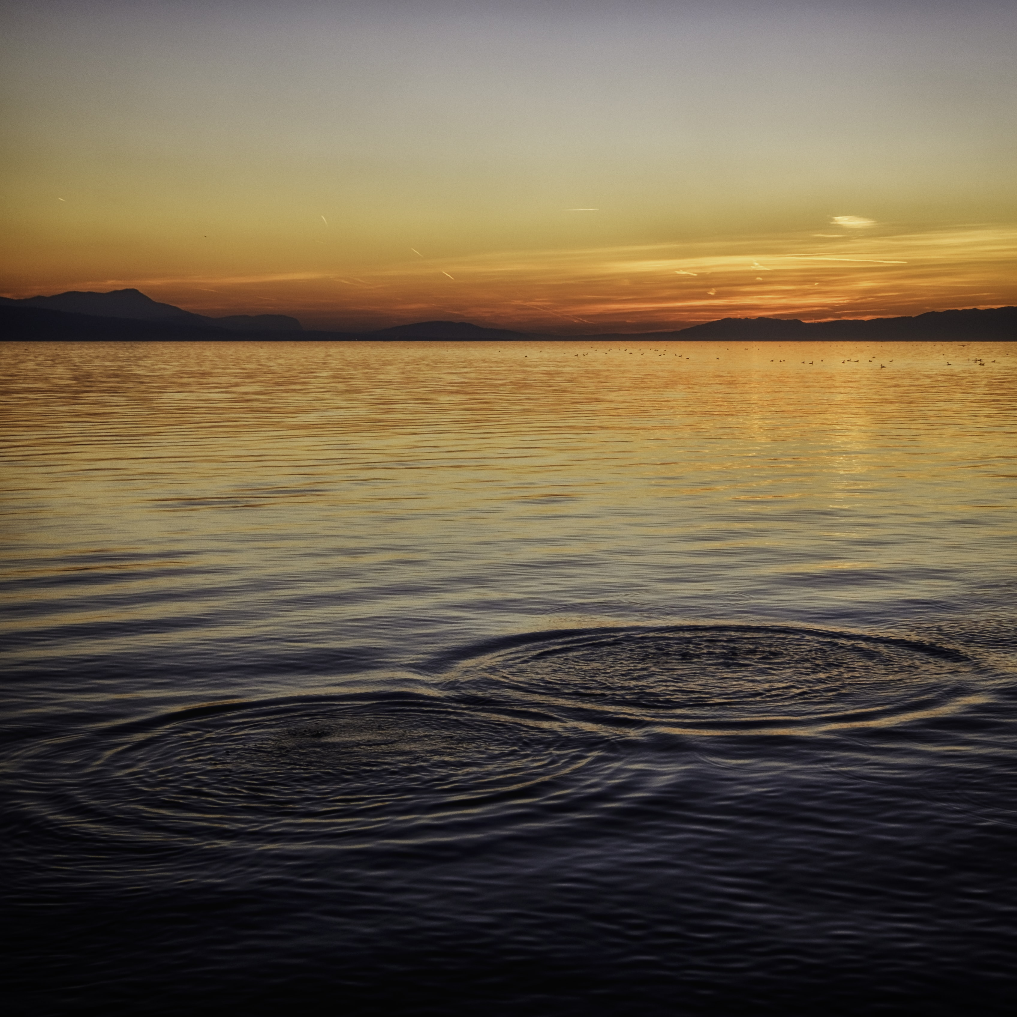 Ripples on the surface of water during sunset with hills in the distance