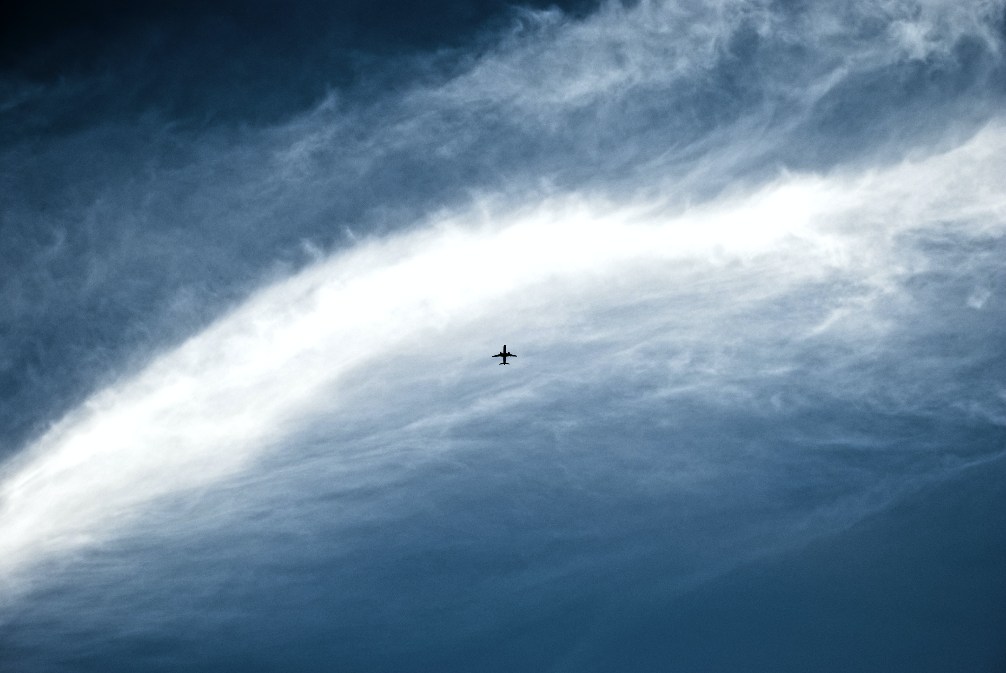 silhouette of jet plane on blue sky