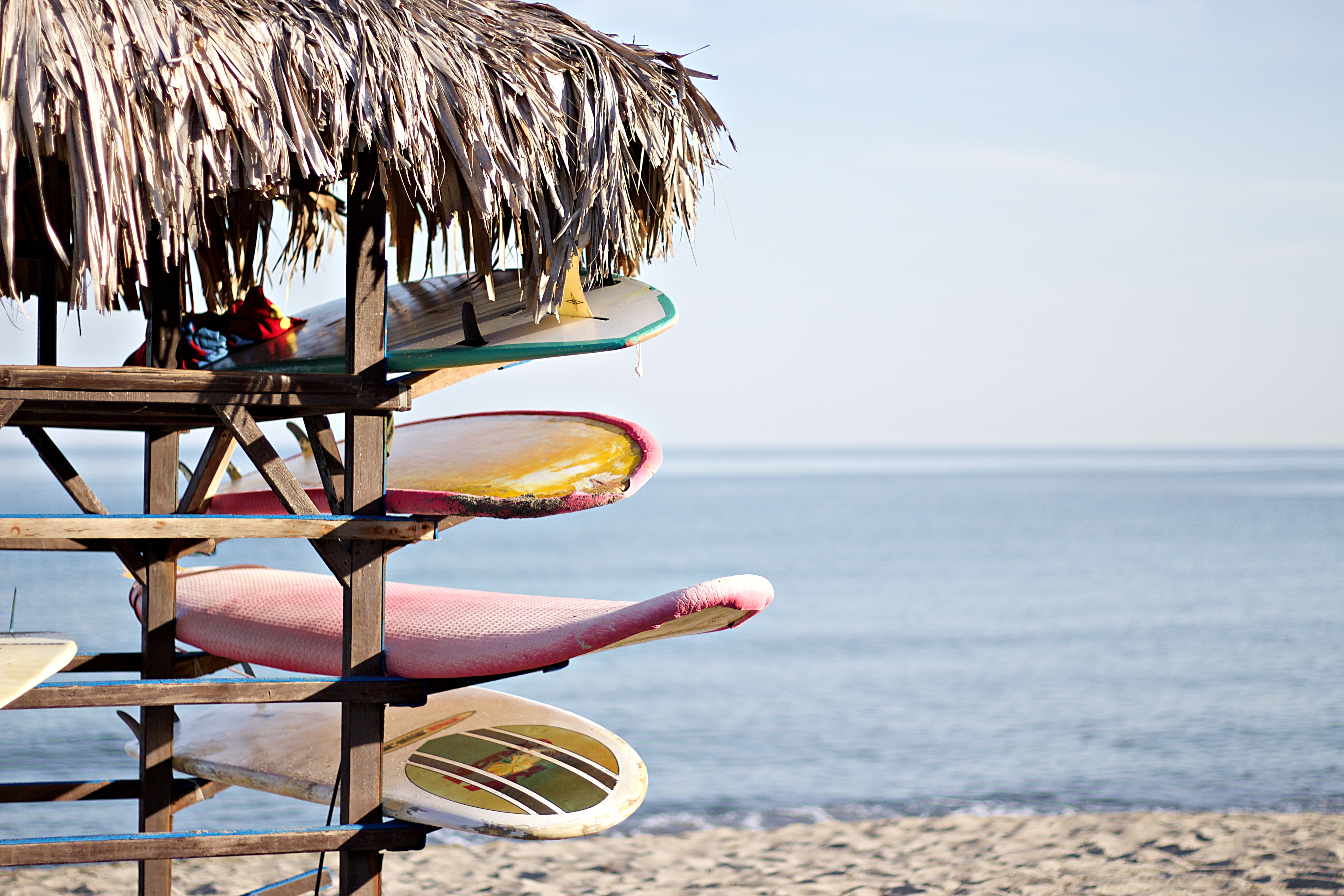 Four surfboards on racks under a thatch roof