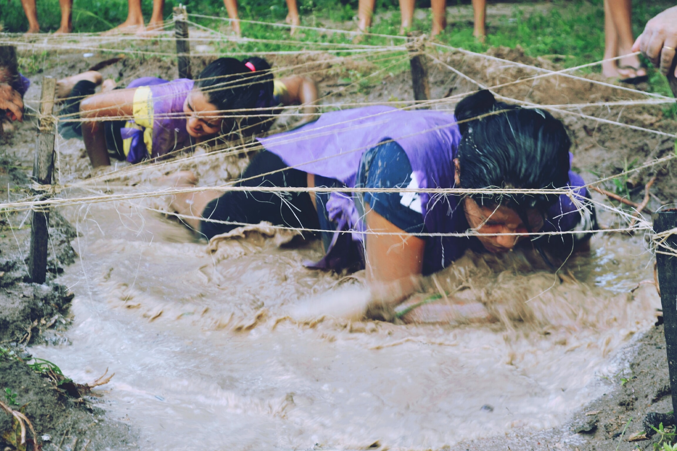 two women crawling on mud with rope
