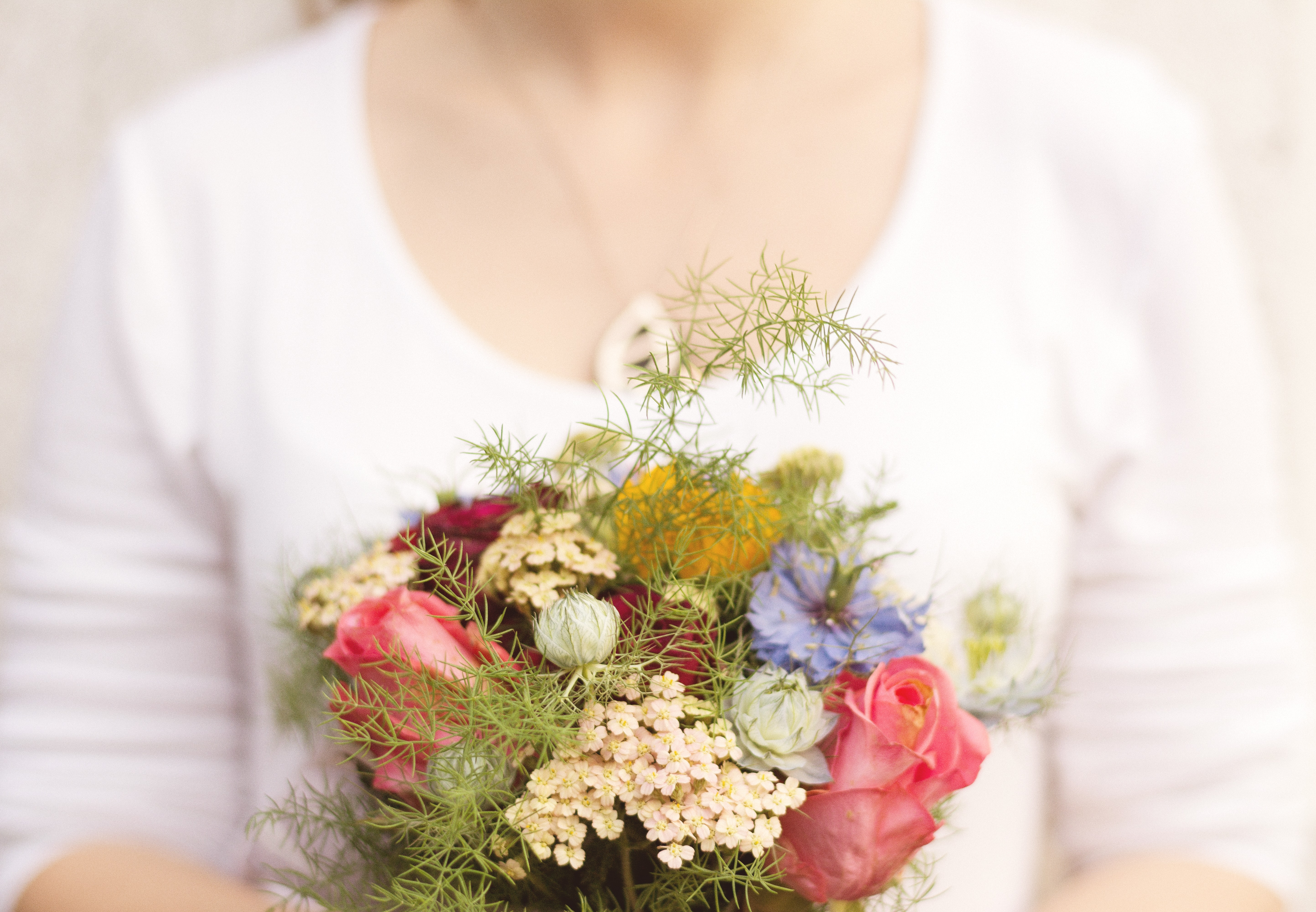 A woman holding a modest bouquet with various flowers