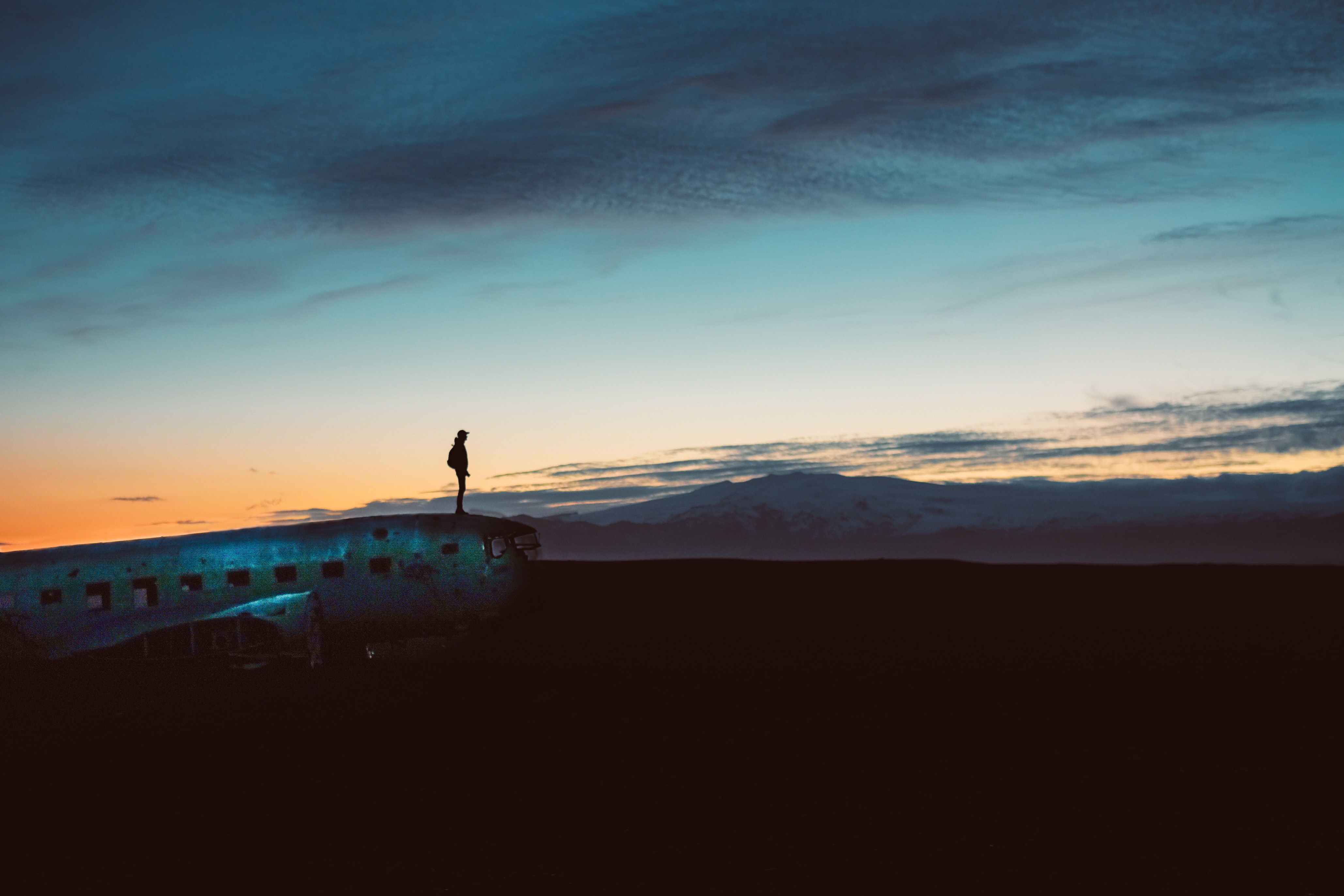 silhouette of a person wearing hat standing at edge of aircraft during a cloudy sunset