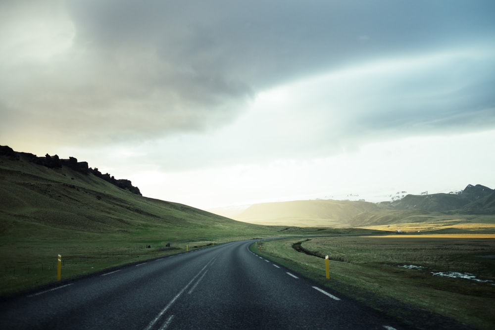 white line open road under cloudy skies