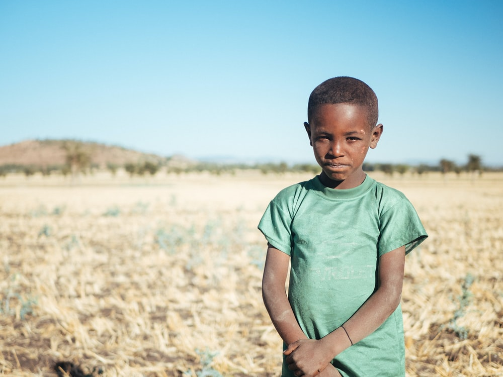 boy standing and holding his arm