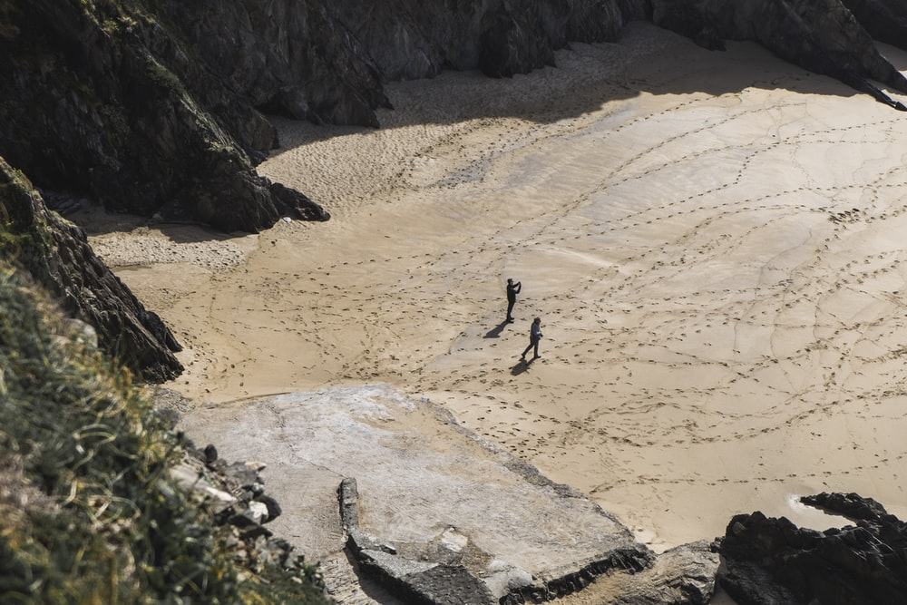 two people walking on desert