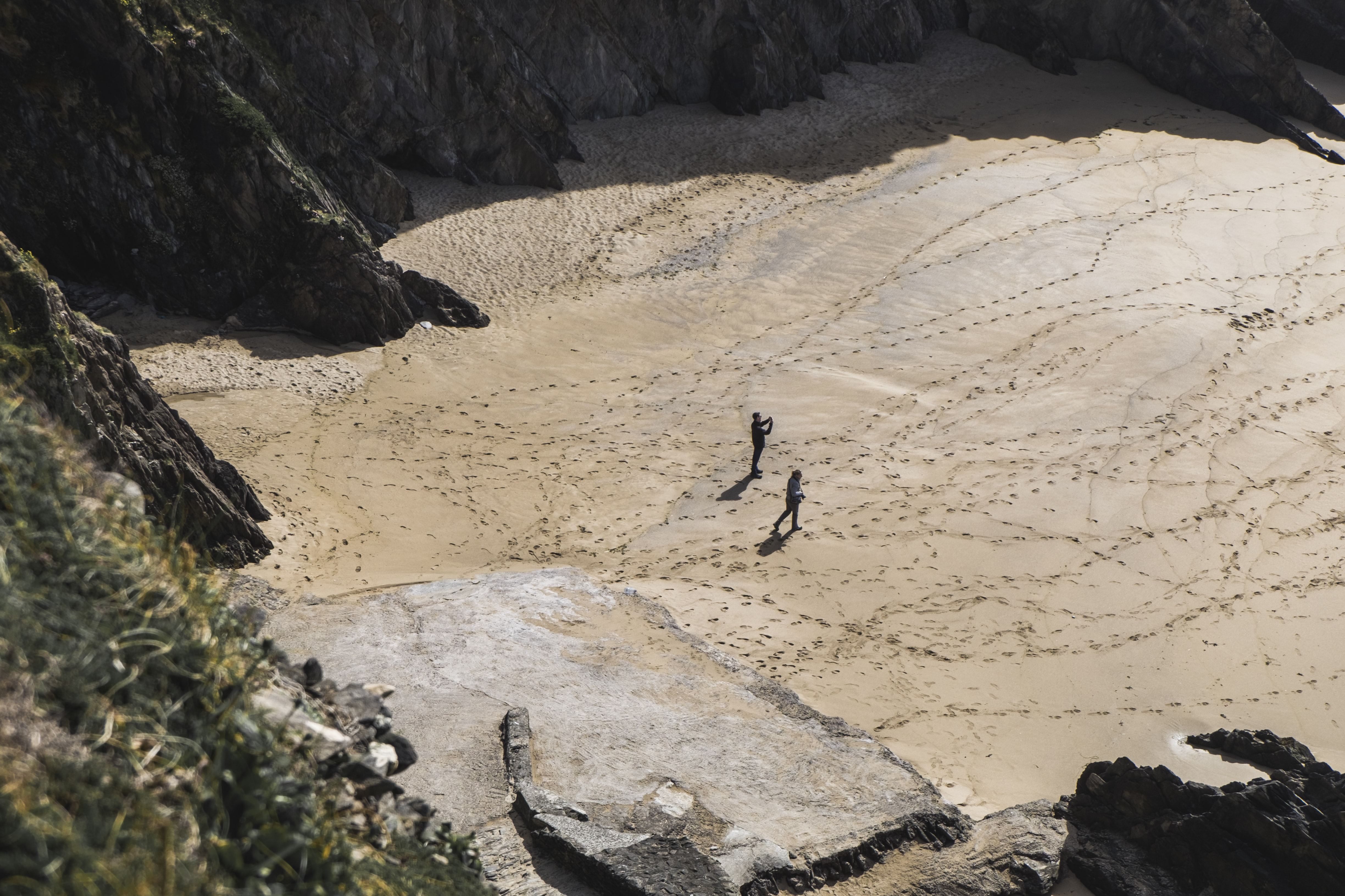 Two people on a sand beach full of footprints between rock cliffs