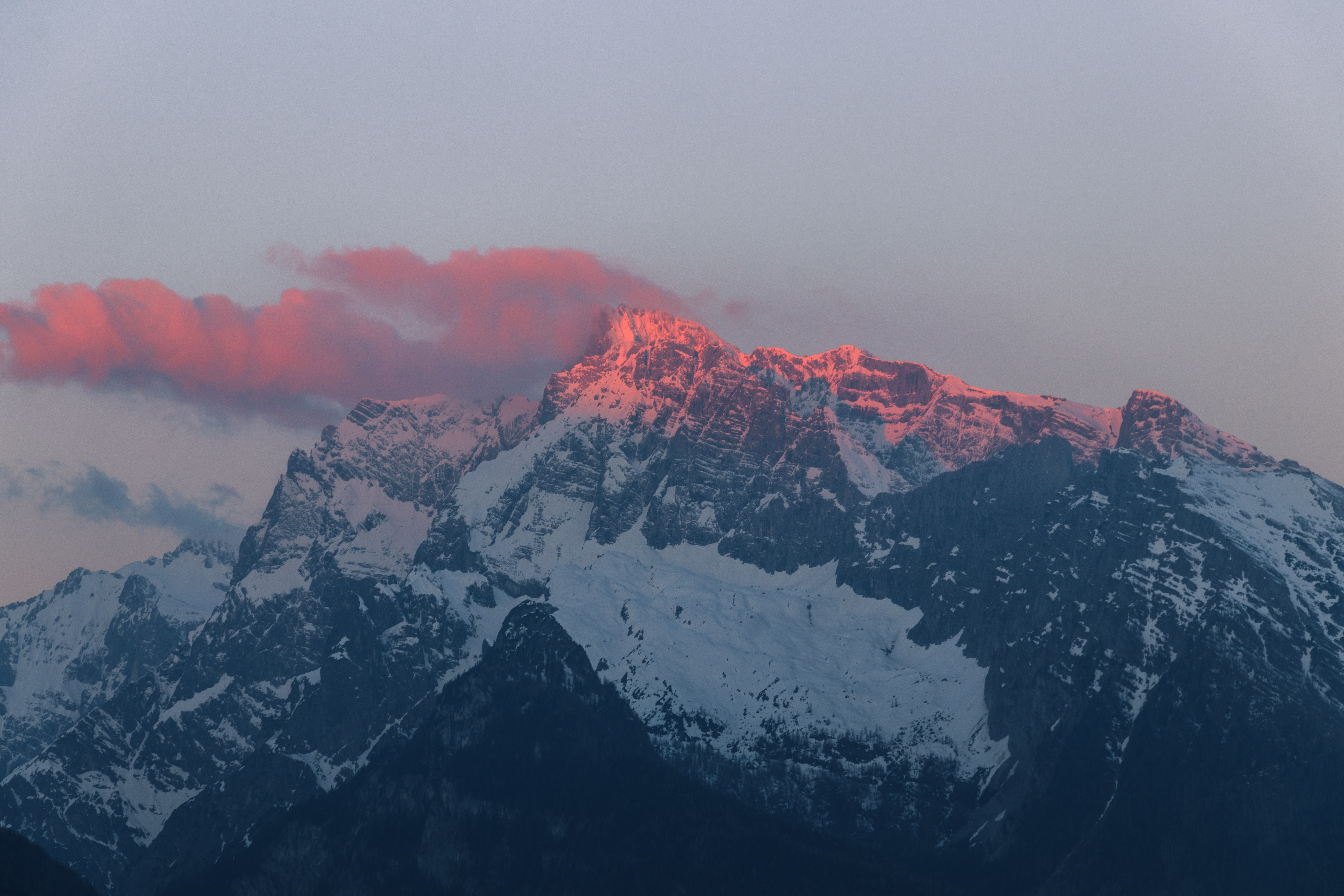 Red sunlight falls on the crest of a mountain during dusk