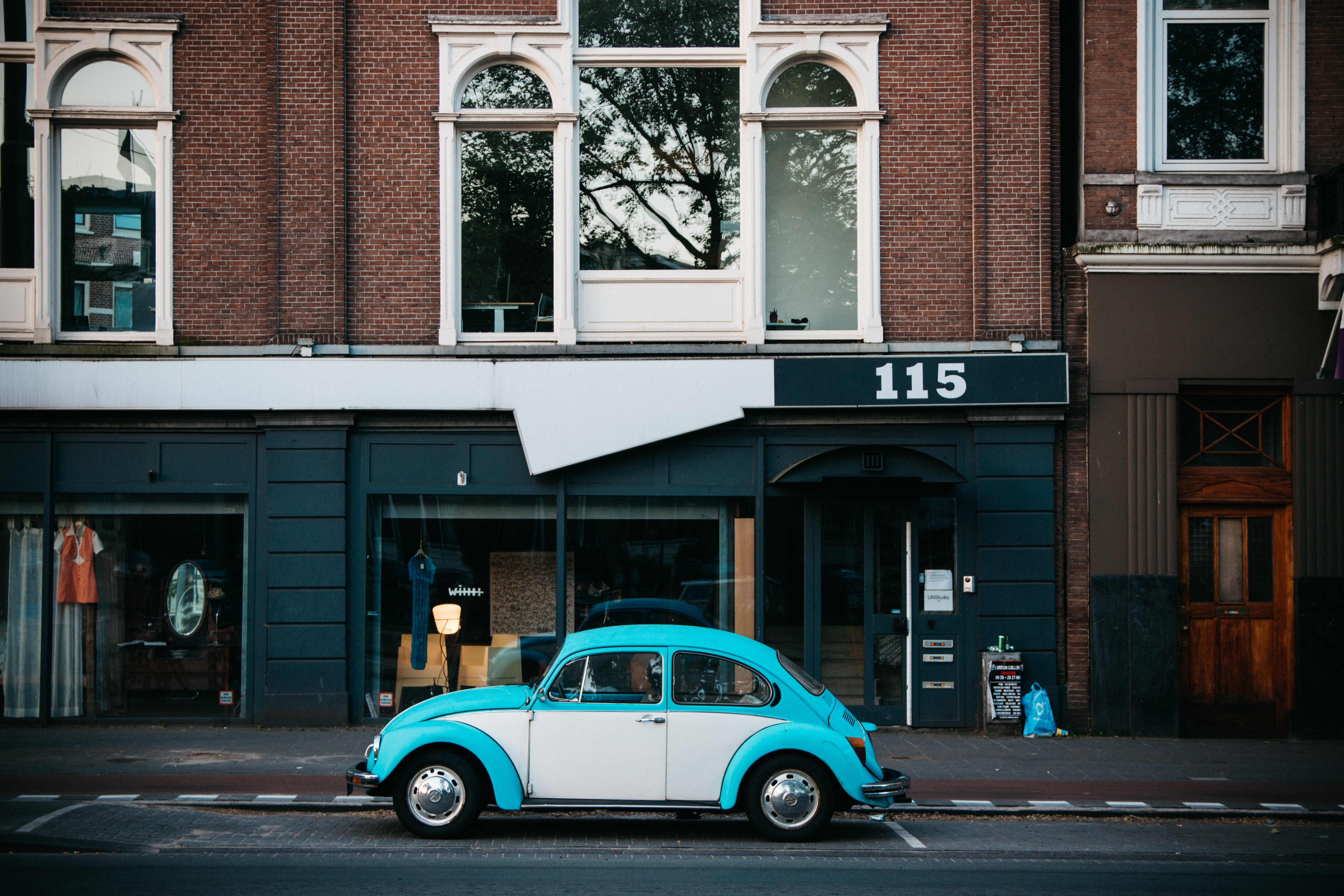 Volkswagen Beetle parking near building beside road