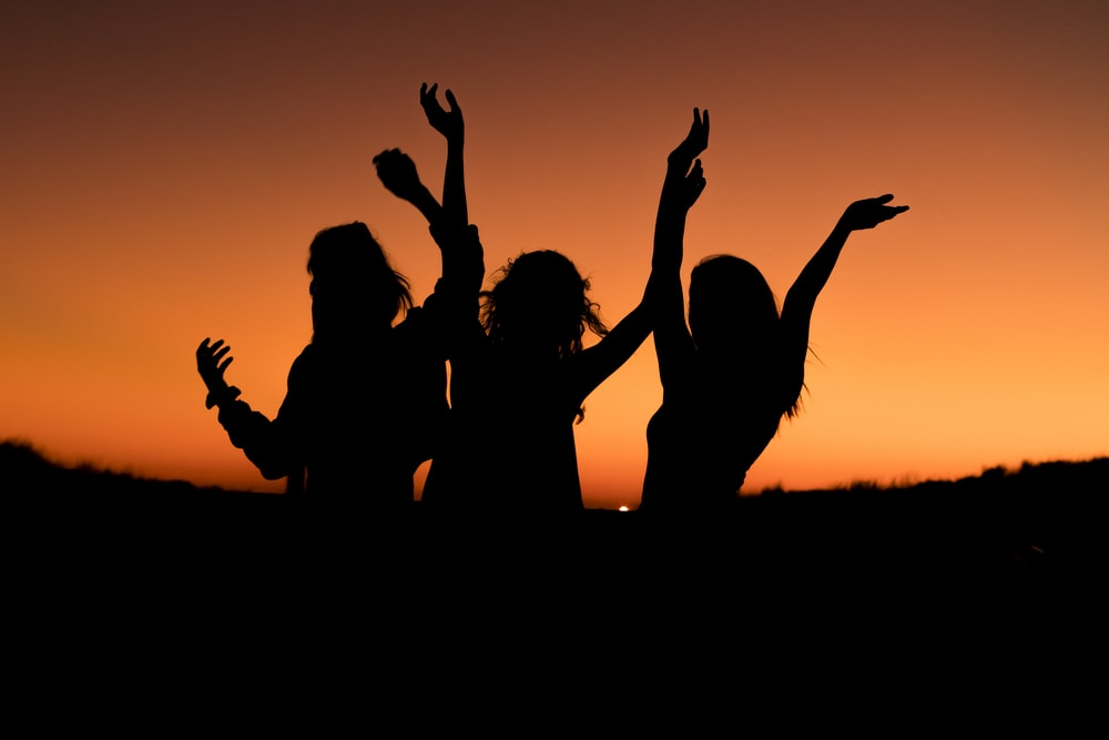 silhouette of three woman with hands on the air while dancing during sunset