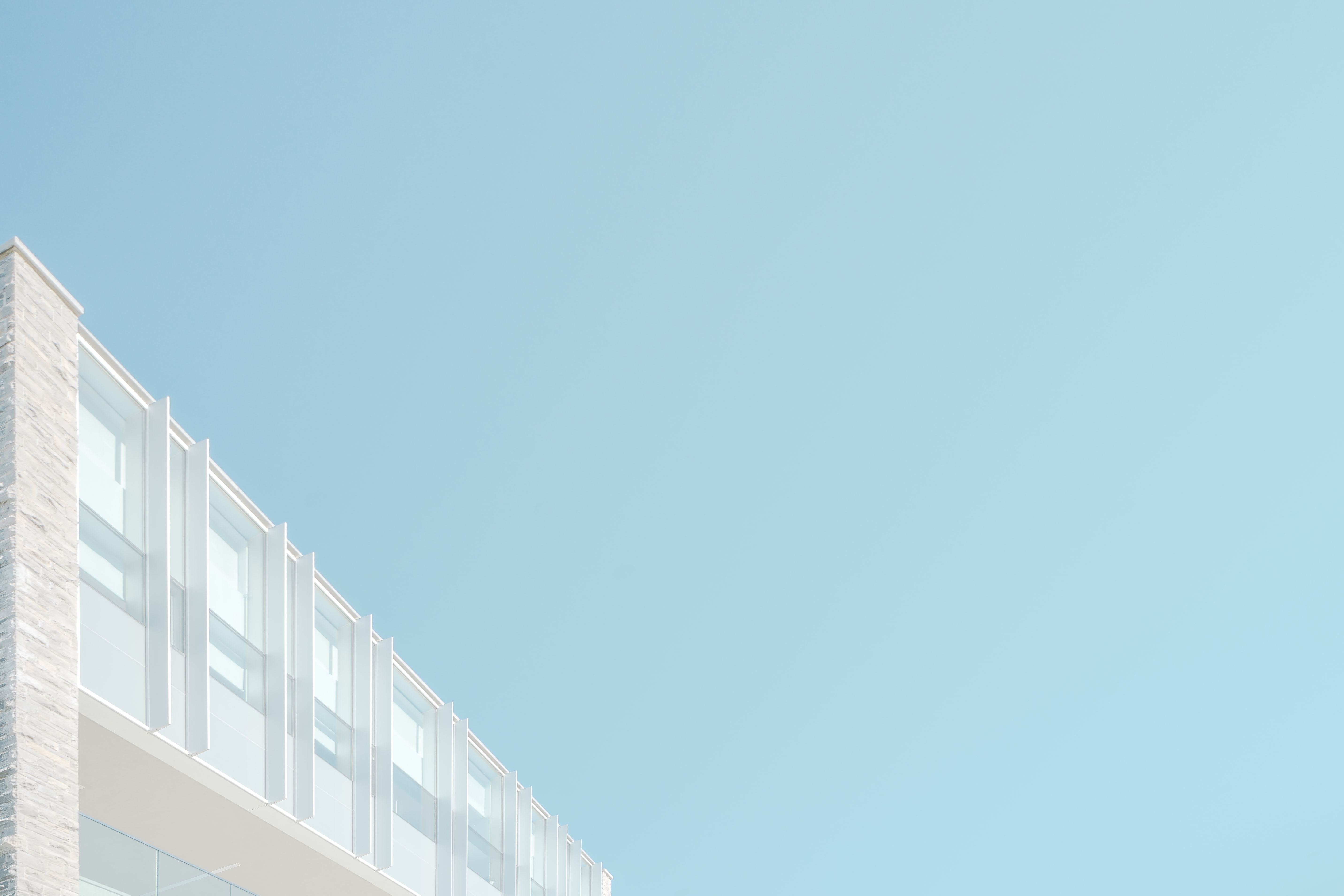 The top of a white modern facade under pastel blue sky