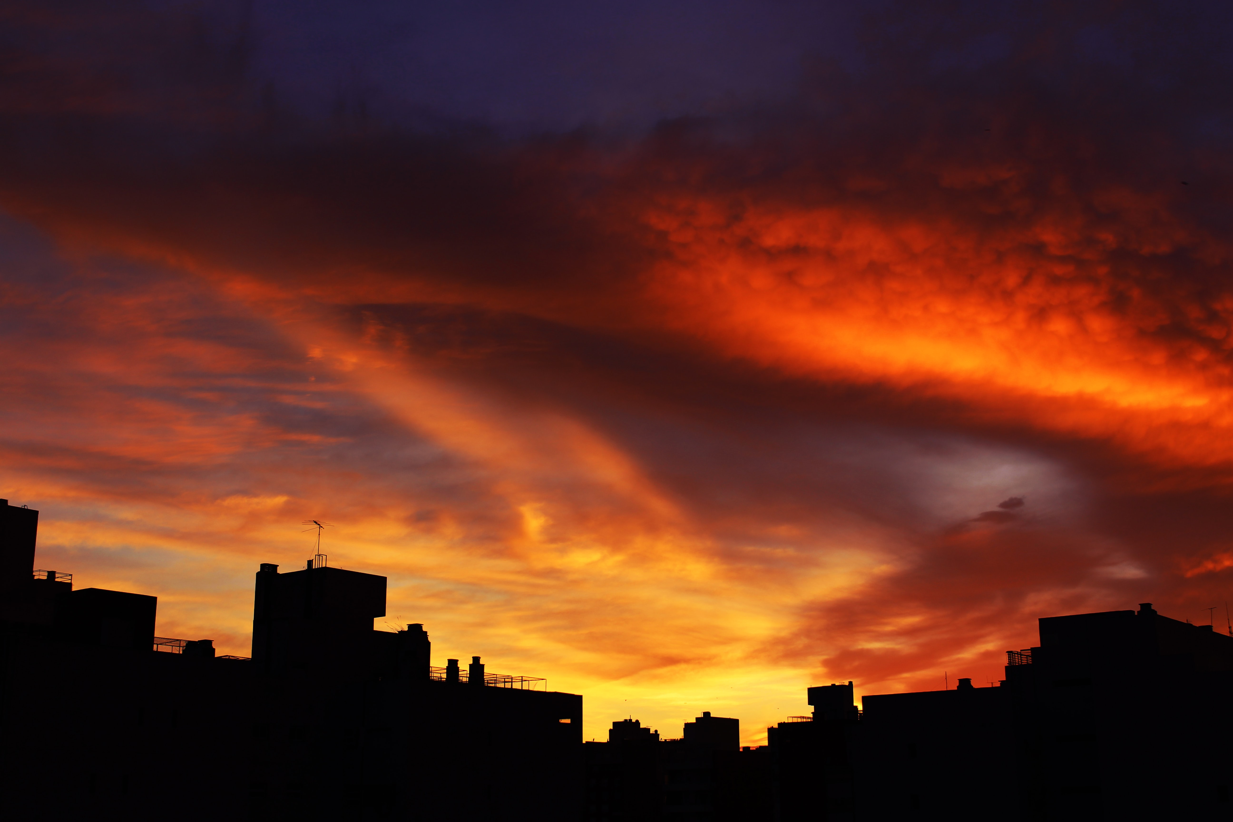 Red and orange dark sunset with purple clouds at twilight with the cityscape in silhouette.