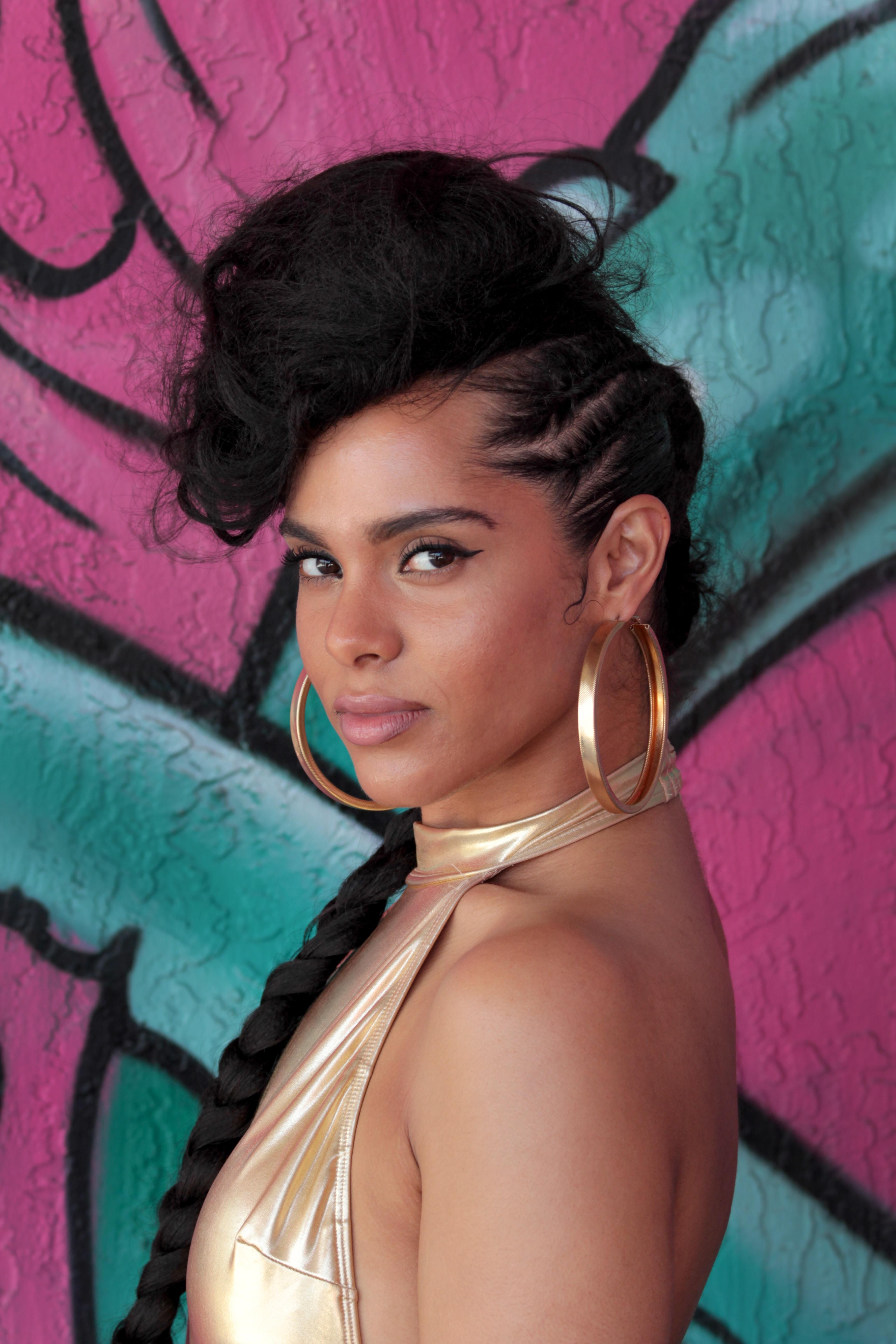 Alicia Keys standing near wall with graffiti art