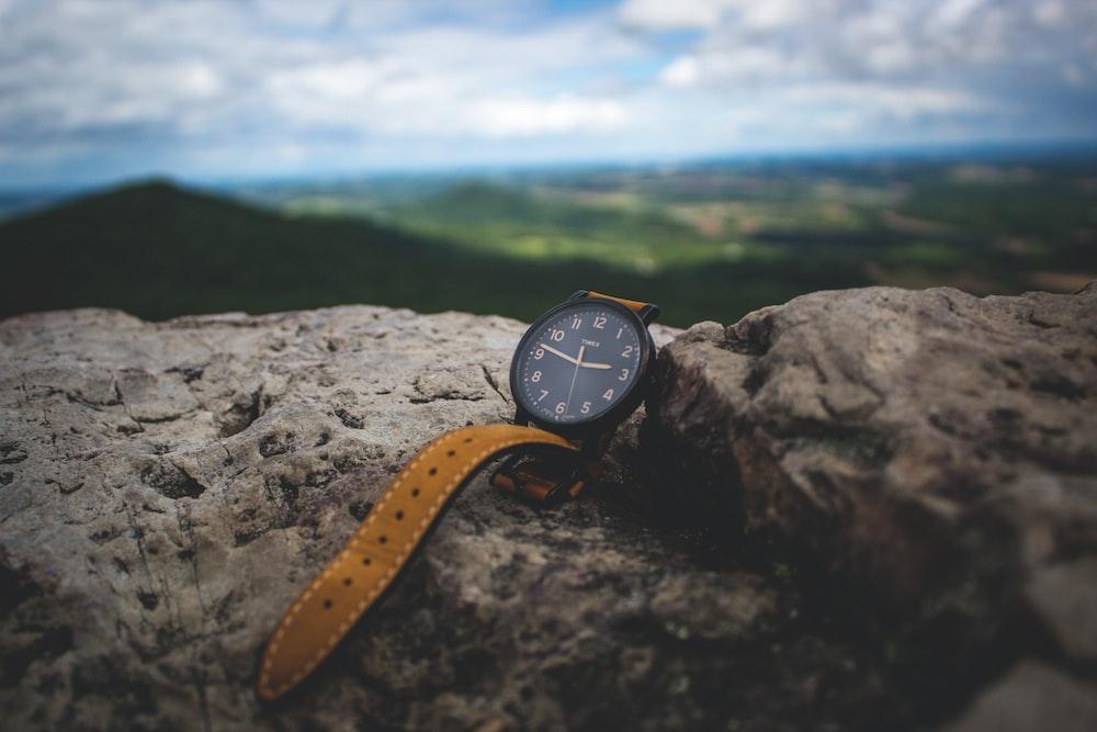round black analog watch on stone