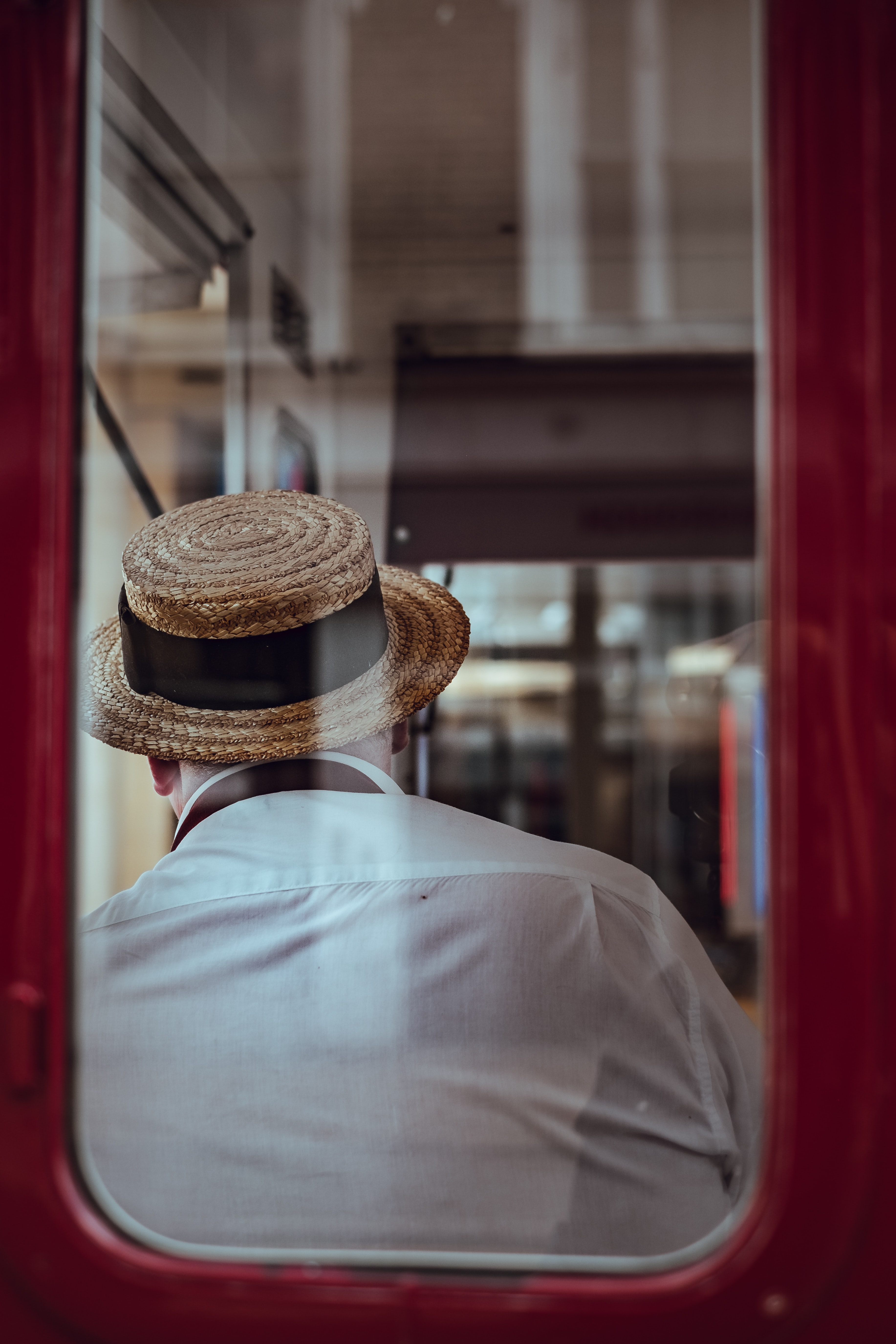 A man in a straw hat leans against a train's window, facing away from the camera