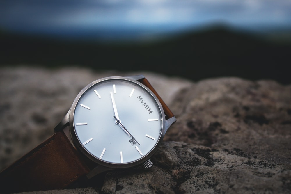 round silver-colored analog watch with black leather strap