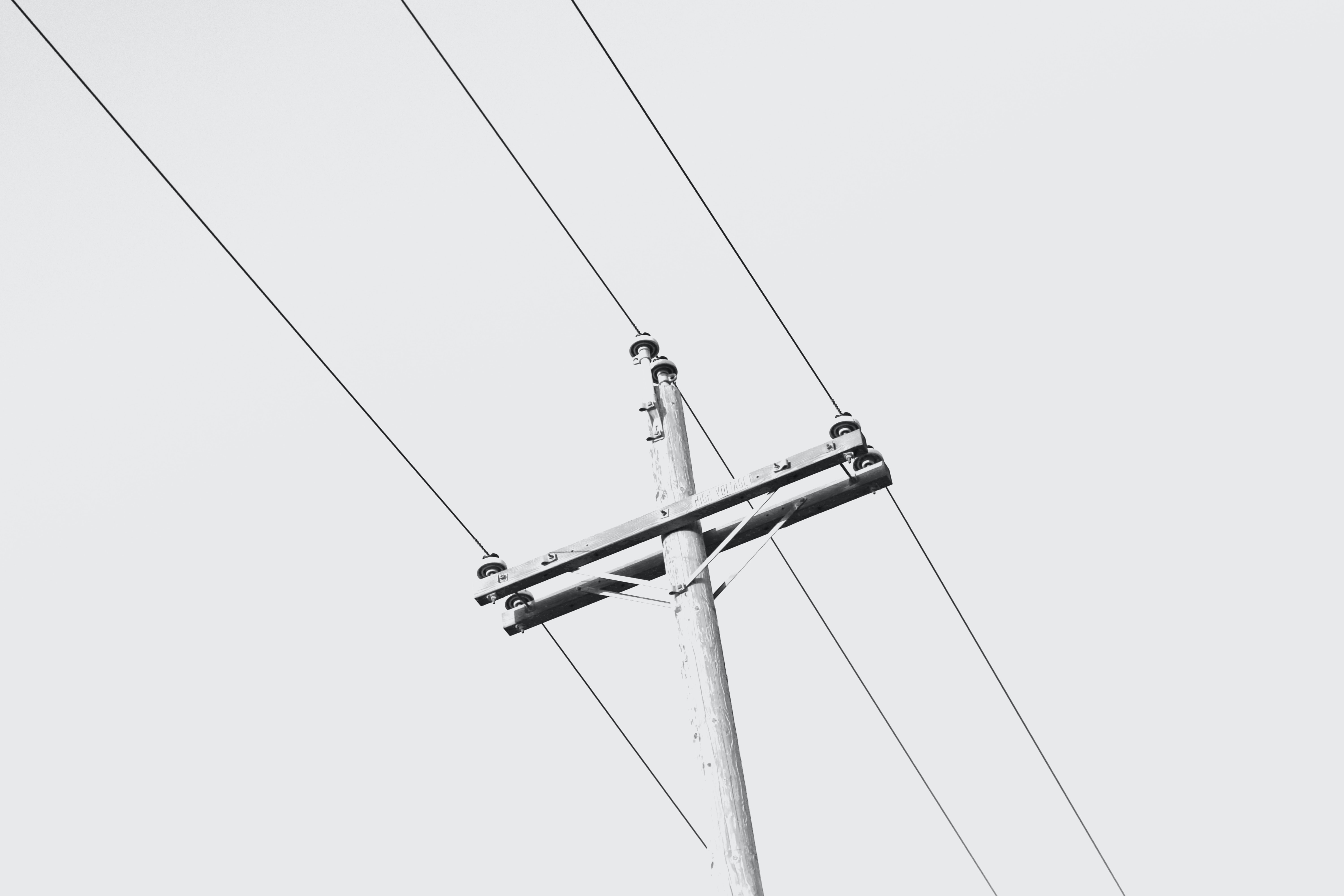 A black-and-white shot of a wooden power pole