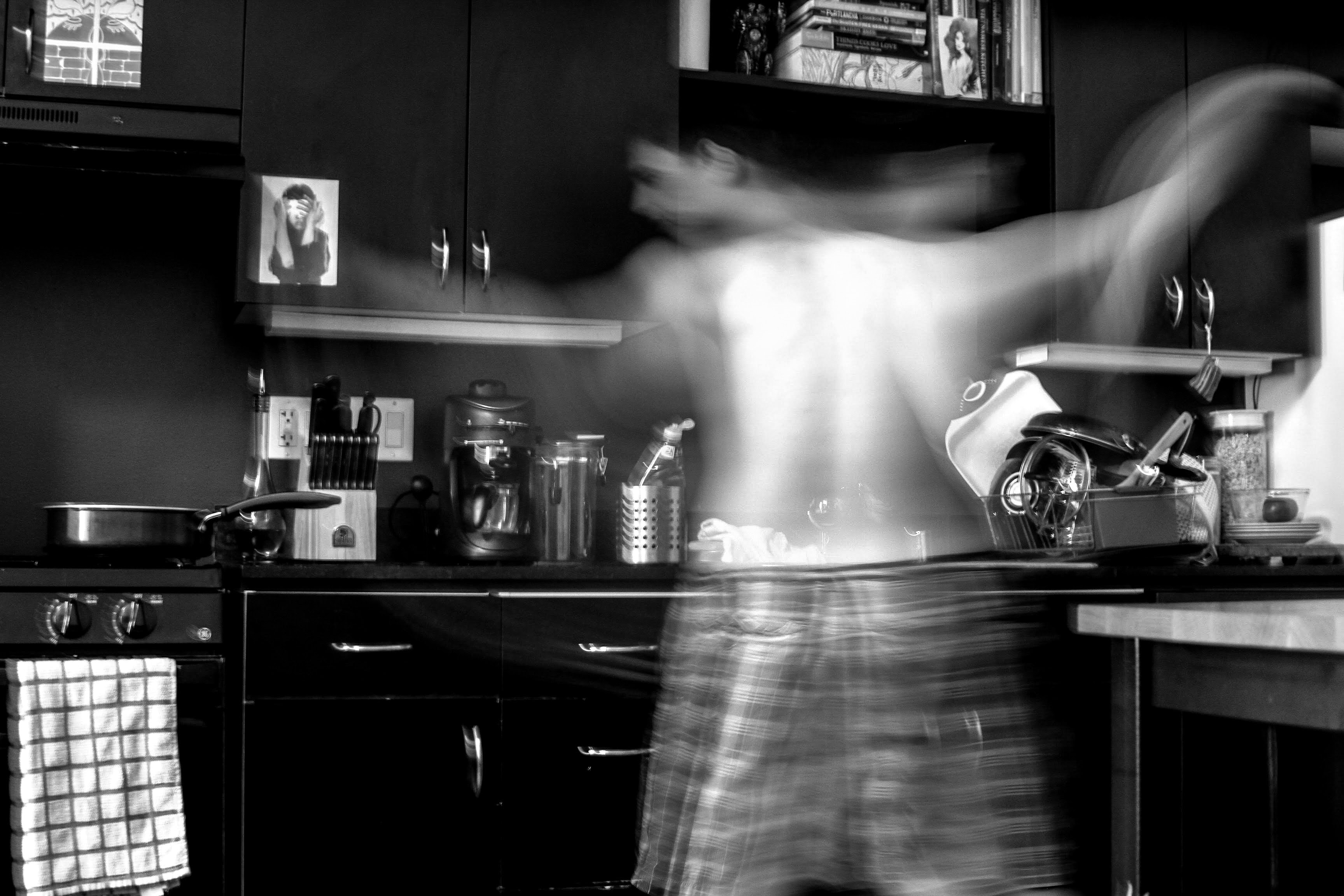 Black and white blurred motion shot of topless man in pyjama bottoms moving energetically in kitchen