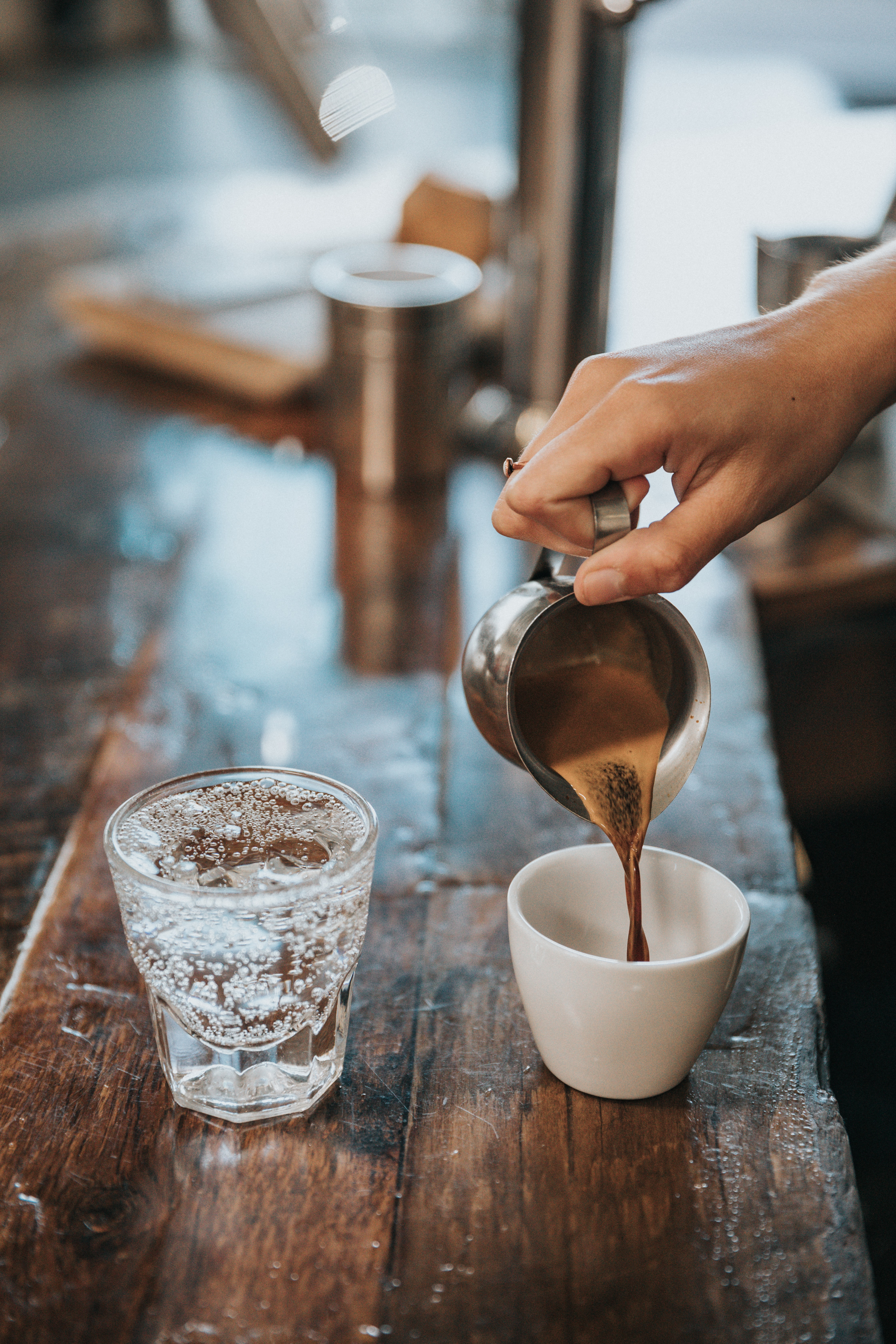 A person pouring coffee into a cup next to a glass of sparkling water