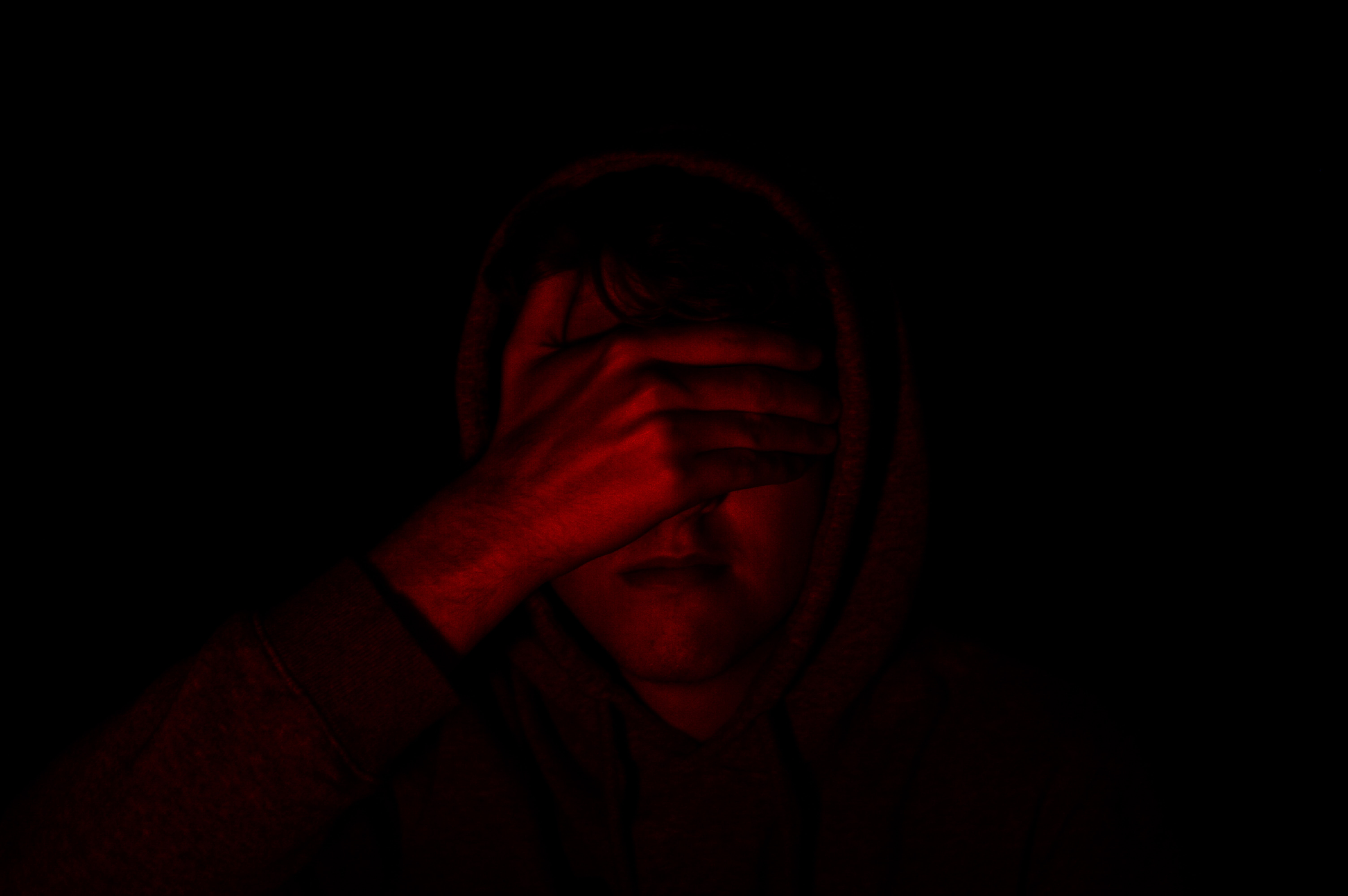 person covering face with right hand