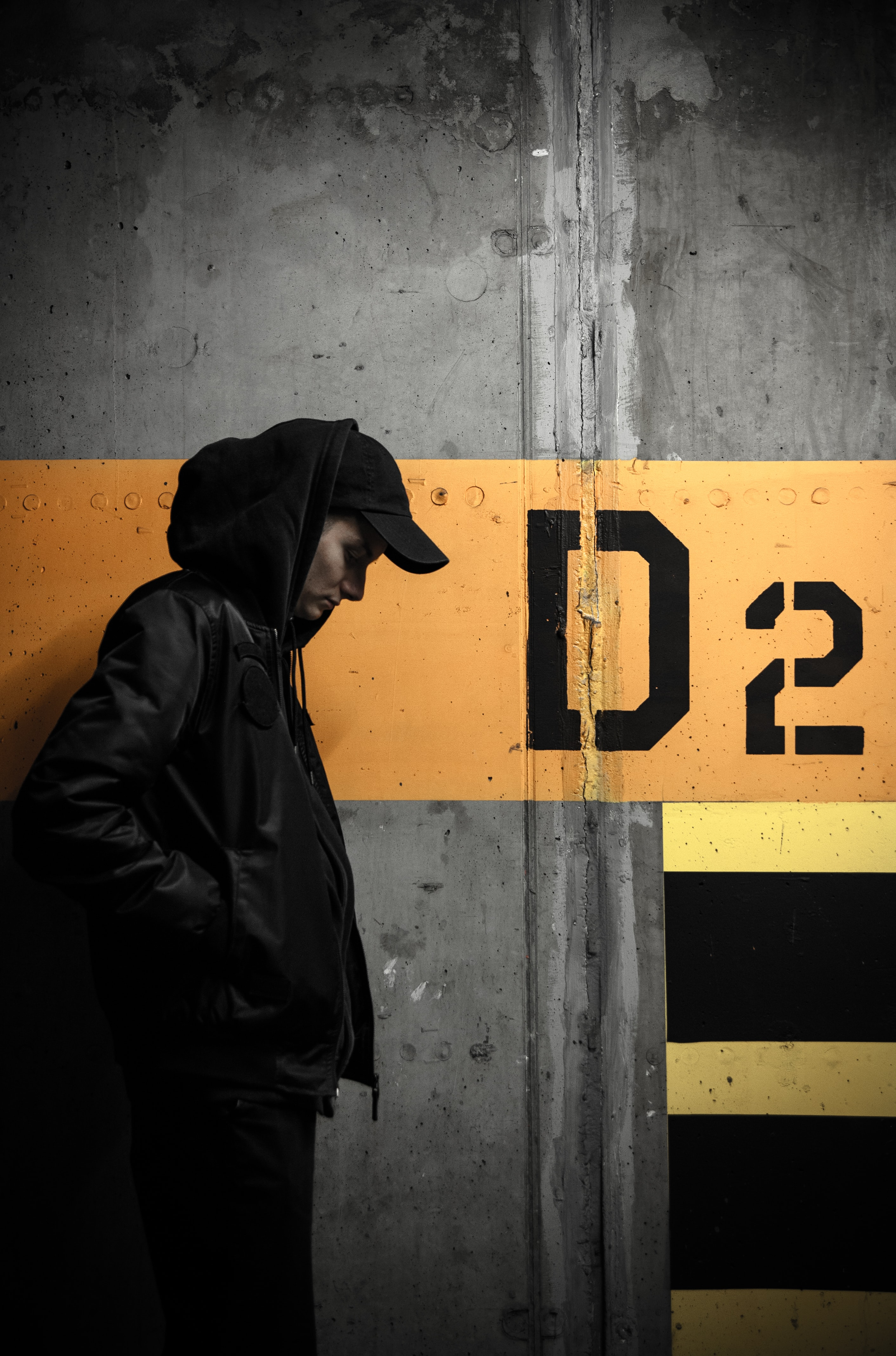 Man with hoodie and cap standing next to a concrete wall