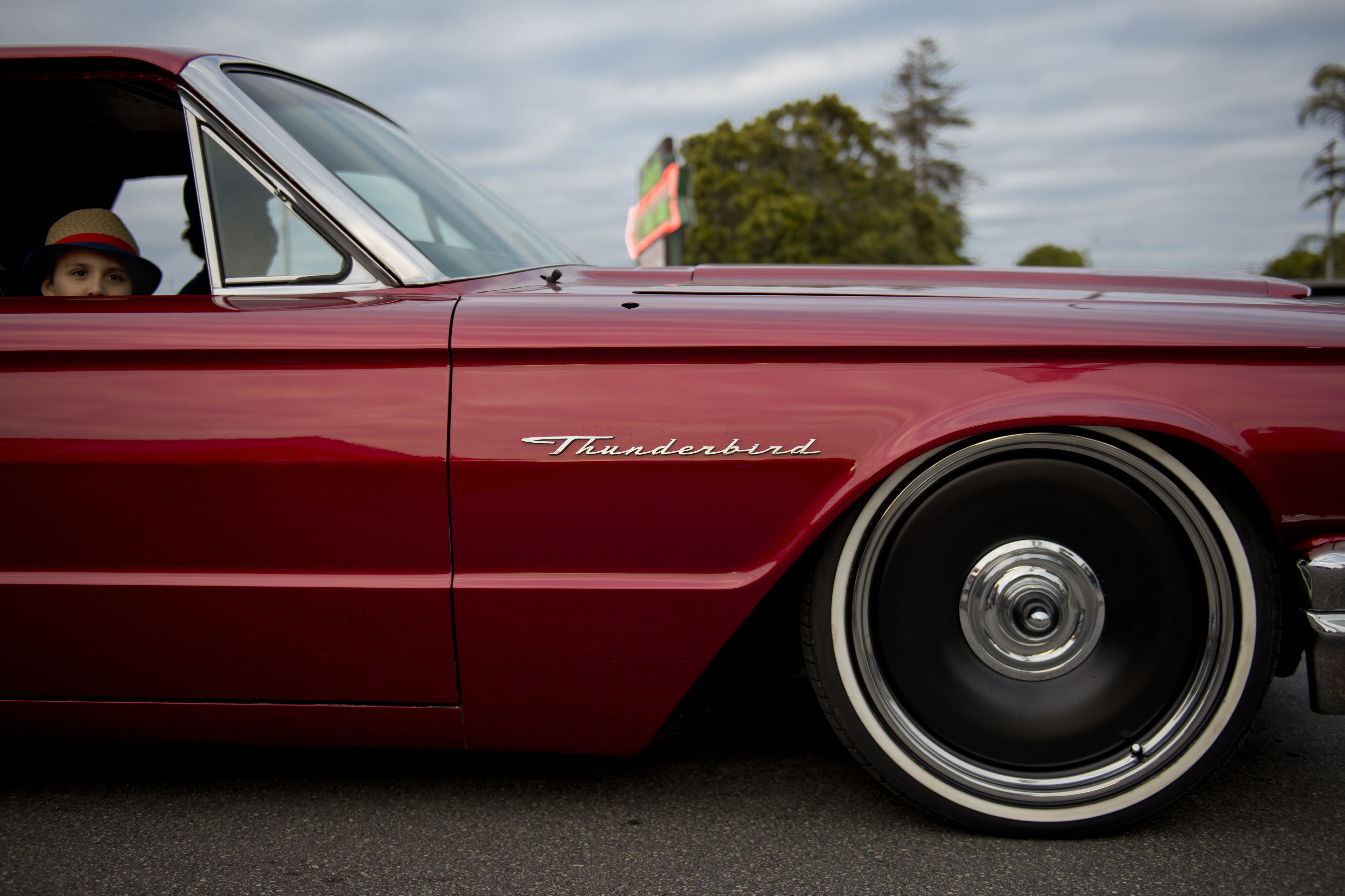 A close-up of a red Ford Thunderbird with a child behind the lowered down window of the passenger seat