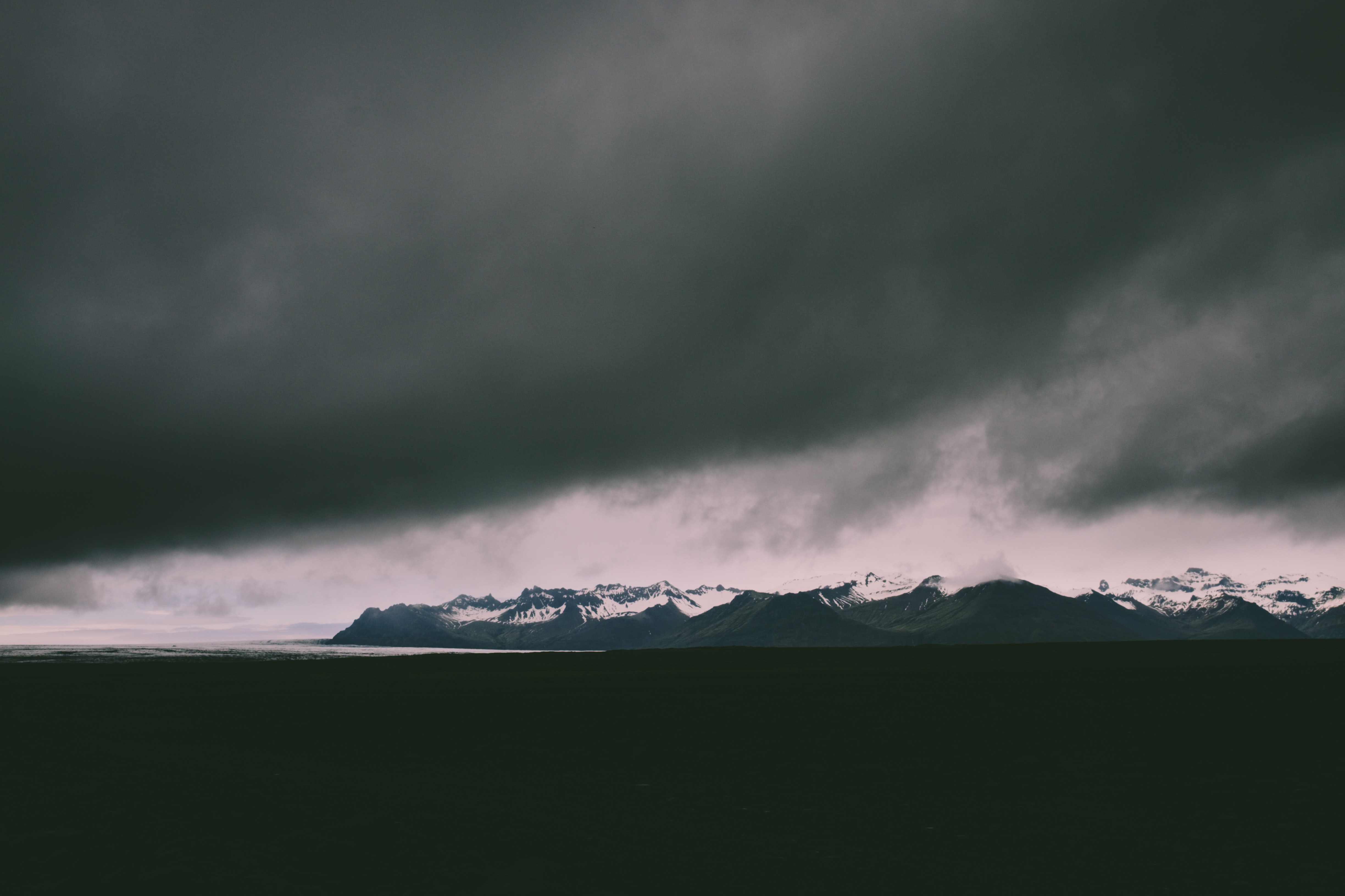 A threatening cloud over a distant mountain range