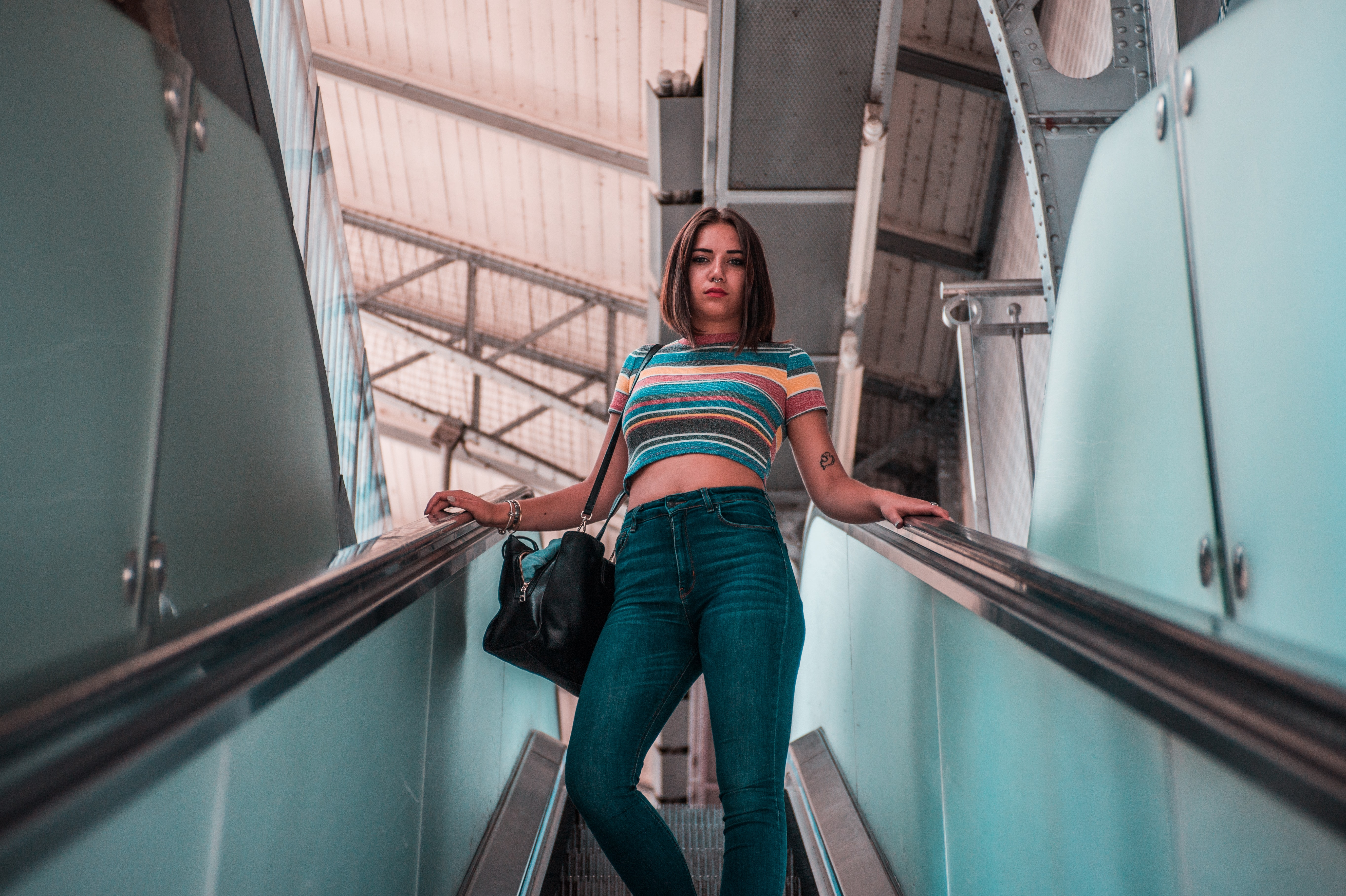 A girl wearing a striped shirt and denim jeans standing on an escalator