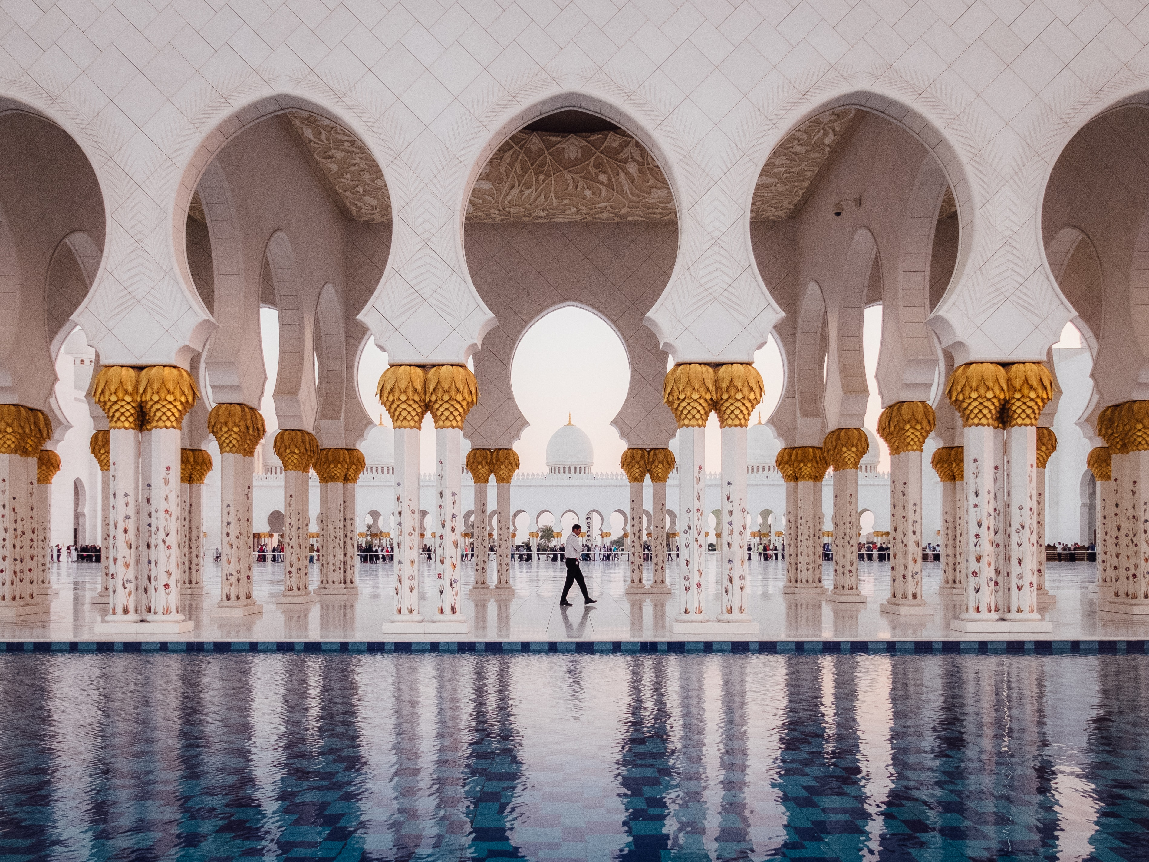White arches and golden pillars make patterns by a reflection pool in a mosque