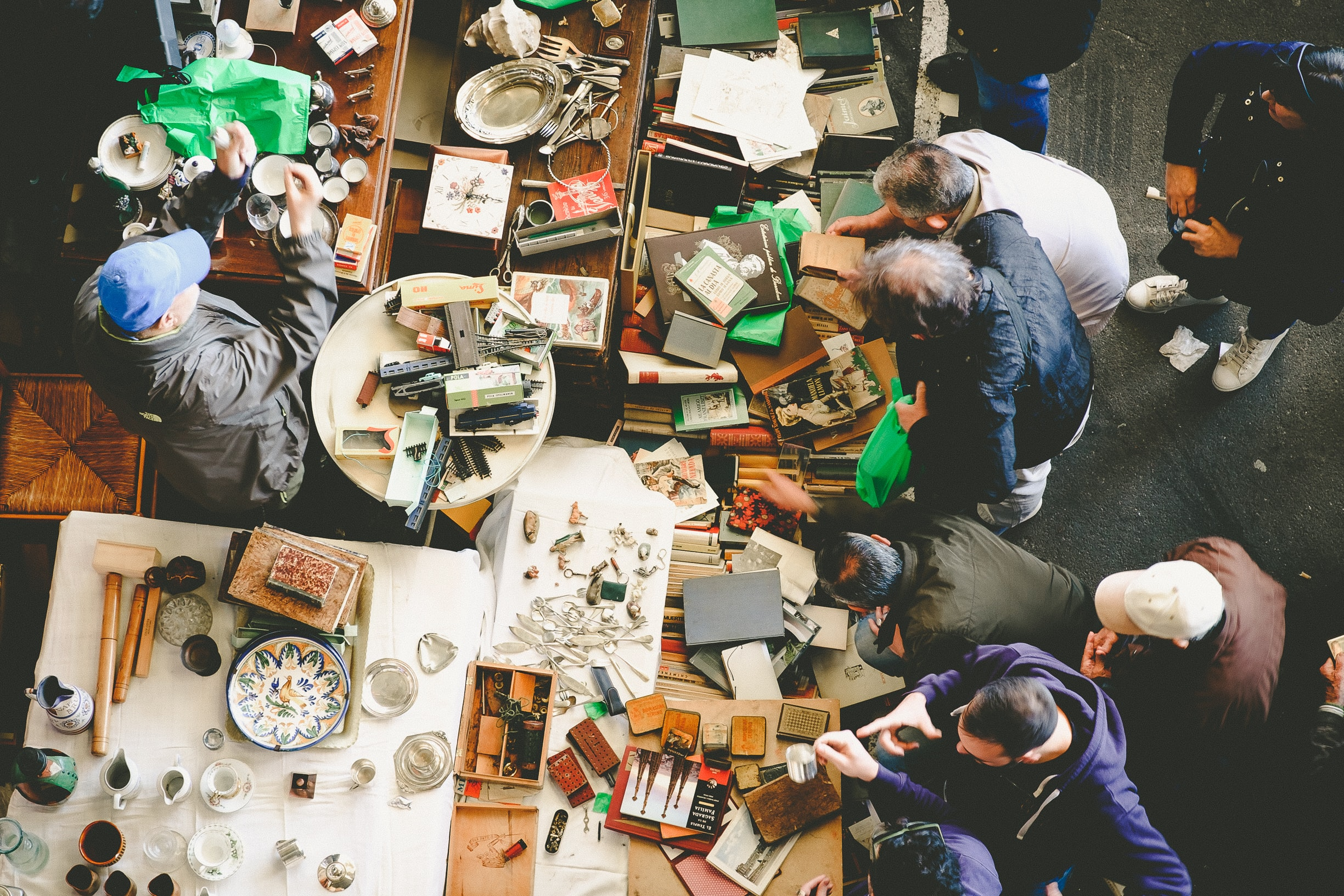 An overhead shot of people browsing books and trinkets at a flea market
