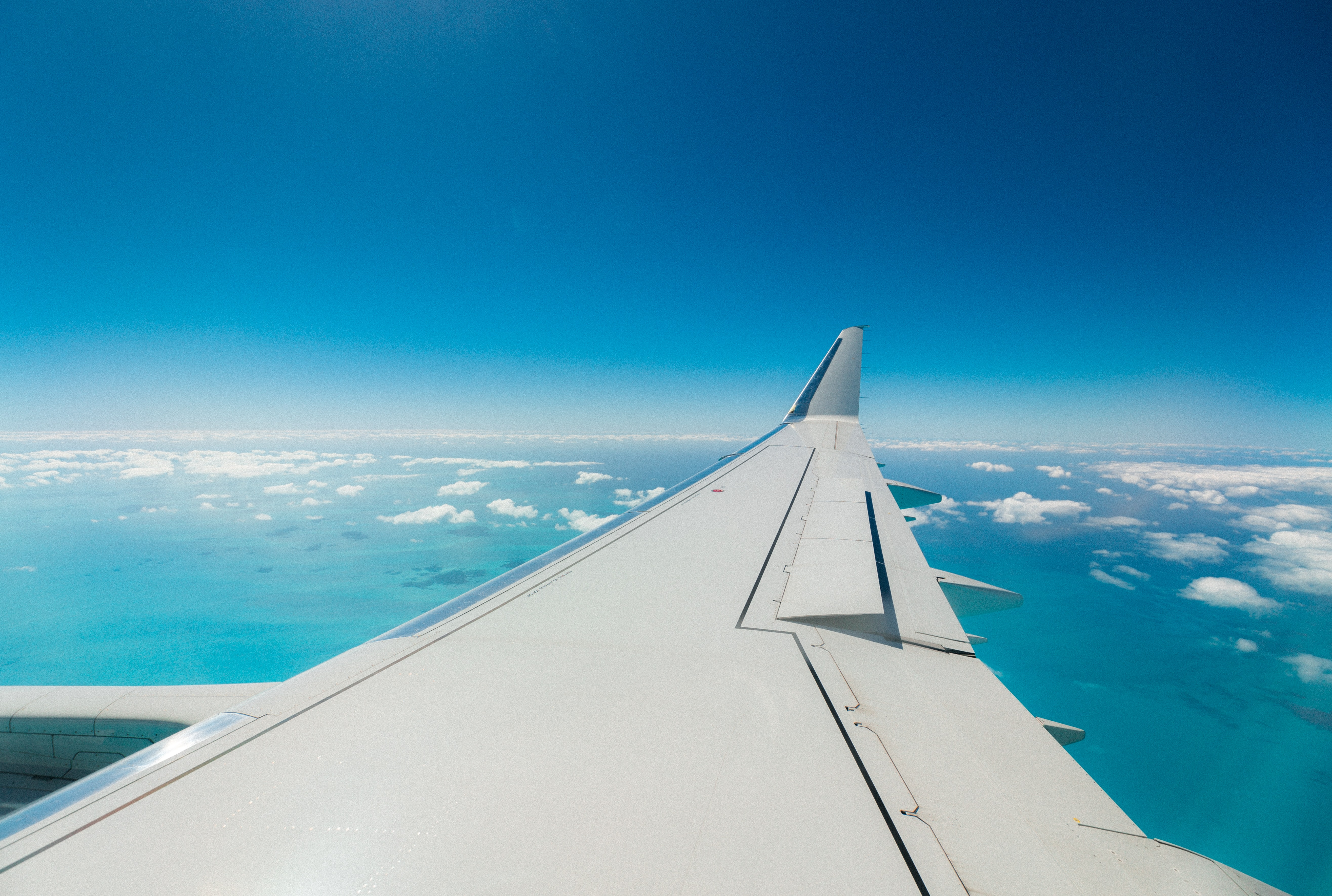 A view from an airplane window on its wing with open wings flaps over patchy clouds