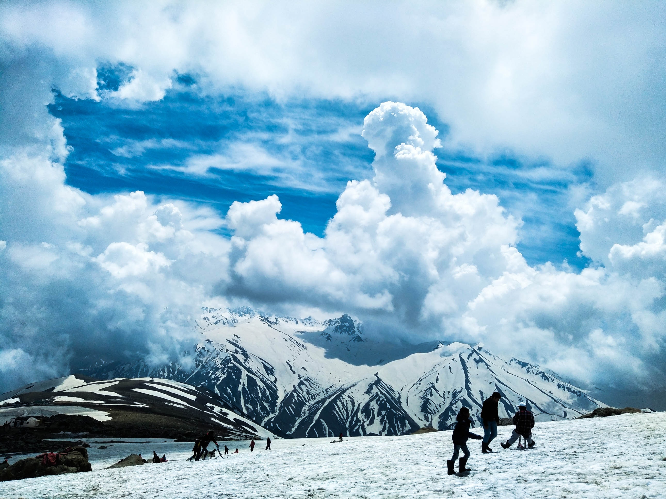 Groups of hikers in a snowy field near a snowy mountain massif on a cloudy day