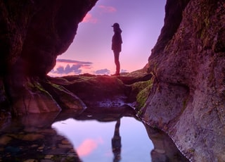 man standing in front of cave