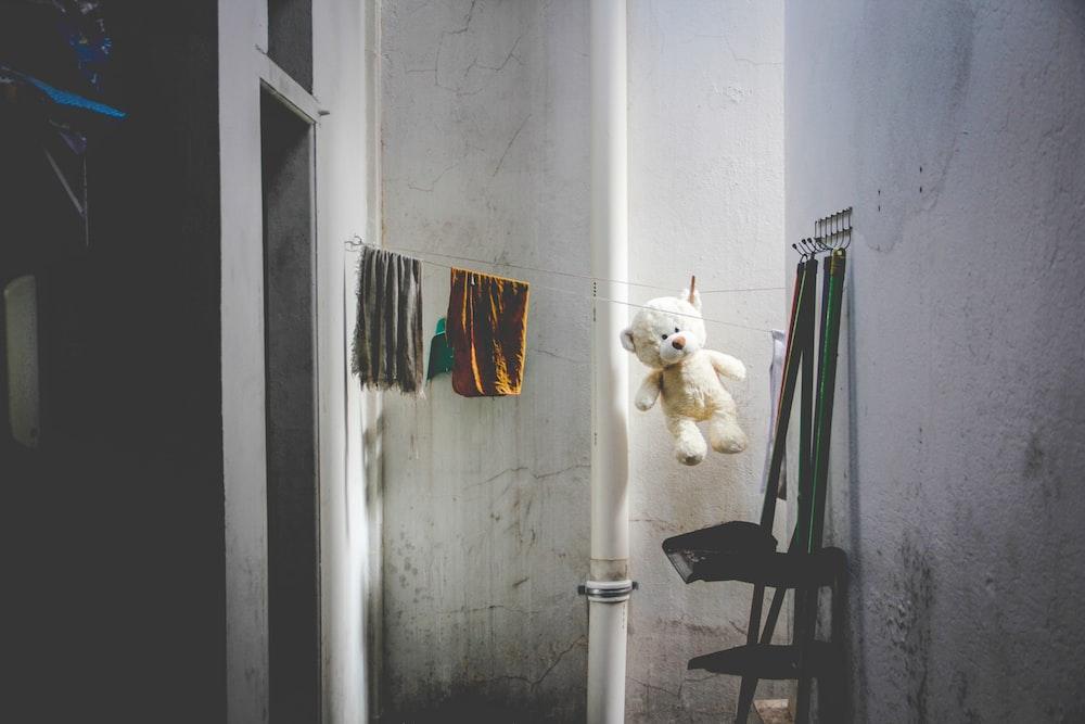 white bear plush toy hanging near white wall