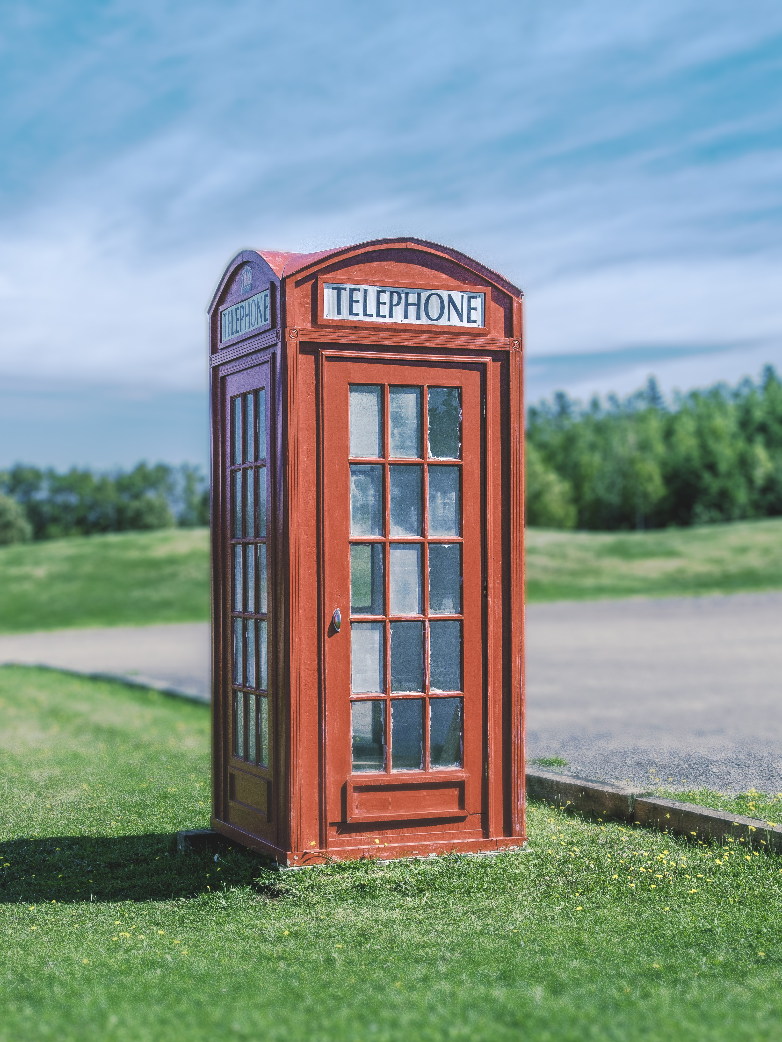 A red telephone booth sits on green grass against a blue sky