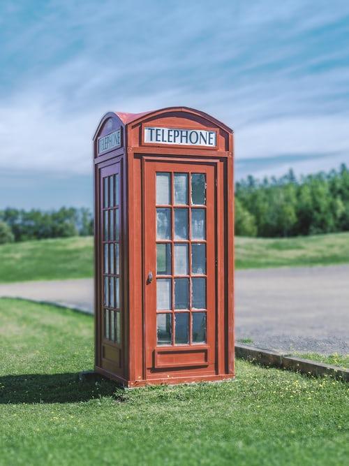 Czerwona budka telefoniczna stojąca na trawie koło drogi